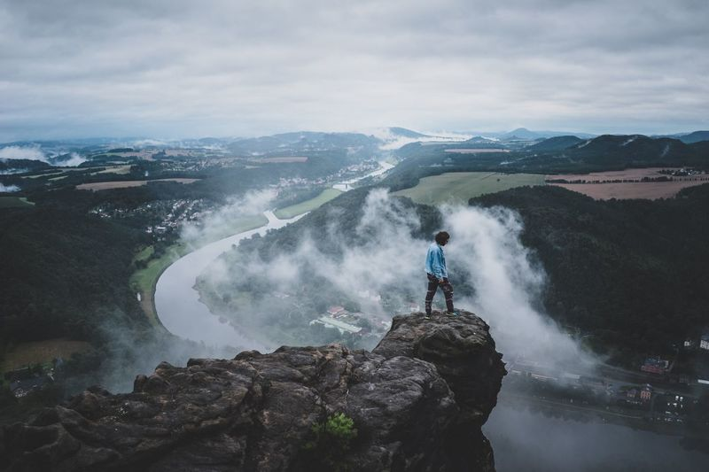 Outdoor shot of guy standing over Elbe river Morning Fog Live Authentic Nature Adventure Roam Lilienstein Saxon Switzerland Elbe River Real People Motion One Person Leisure Activity Beauty In Nature Mountain Nature Sky Rock - Object Water Waterfall Adventure Scenics Outdoors Full Length Lifestyles Long Exposure Cloud - Sky Standing Day