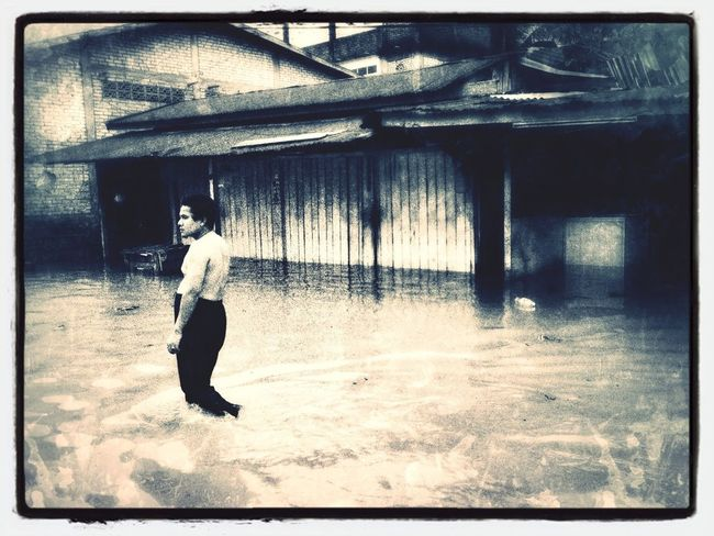 A man walking in floodwater at Sg Kolok, Rantau Panjang