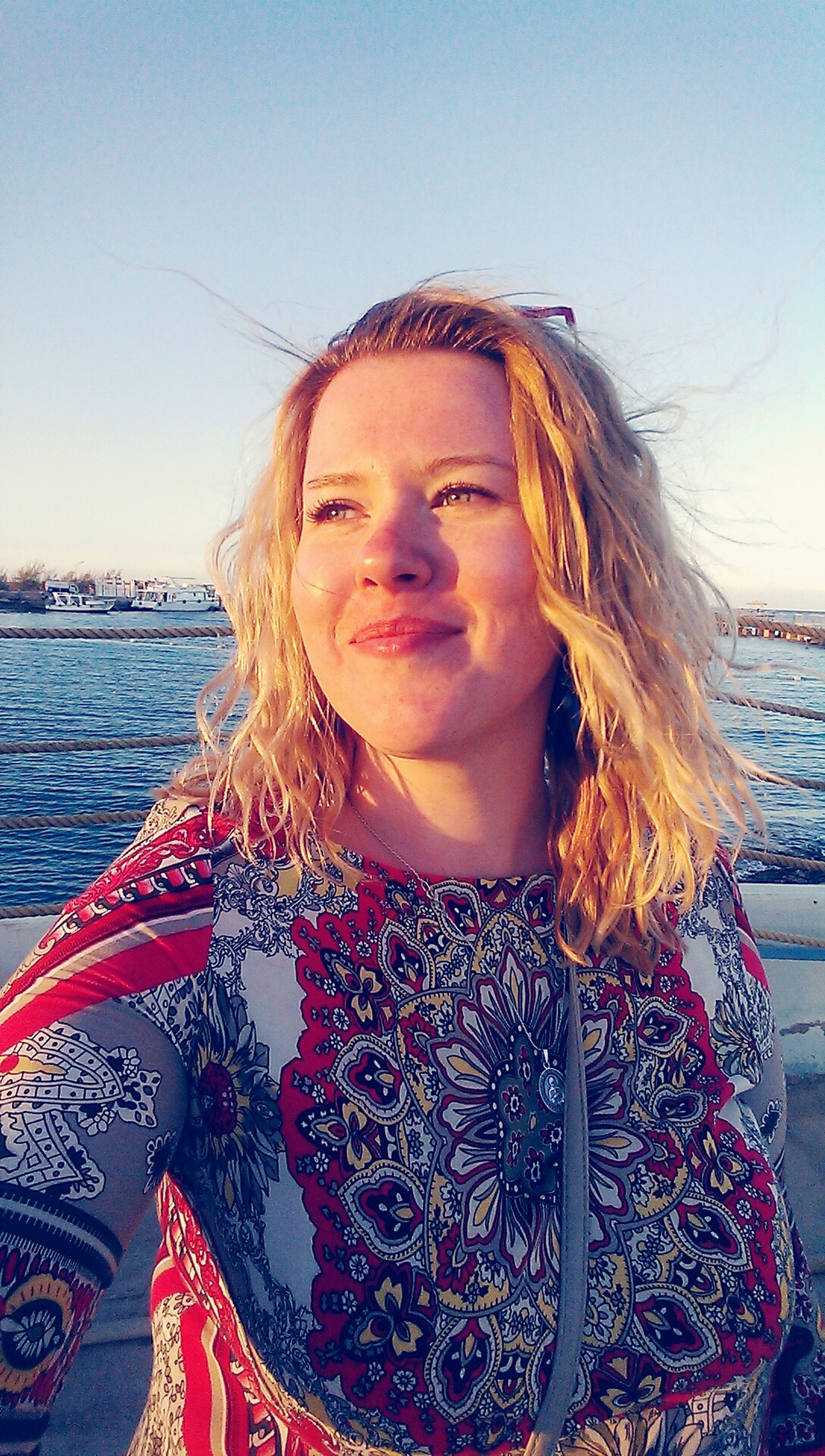 looking at camera, portrait, young adult, person, lifestyles, young women, leisure activity, water, front view, smiling, casual clothing, long hair, happiness, toothy smile, sea, headshot, standing