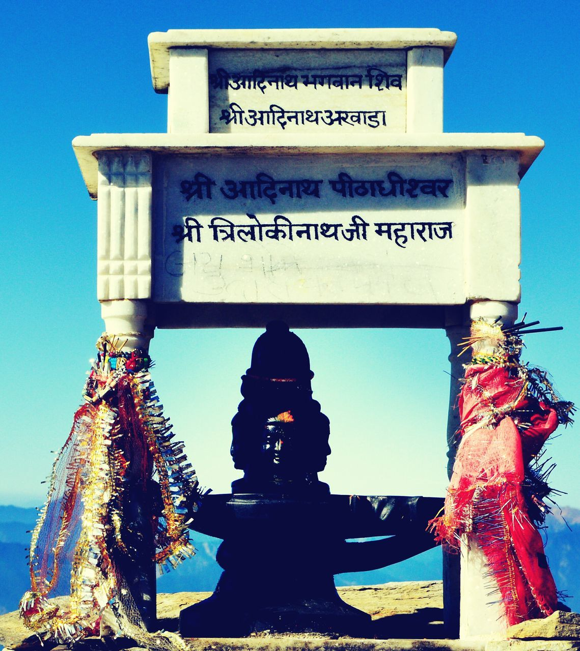 statue, text, human representation, sculpture, spirituality, religion, male likeness, art and craft, day, no people, low angle view, outdoors, place of worship, blue, building exterior, clear sky, sky, architecture, close-up