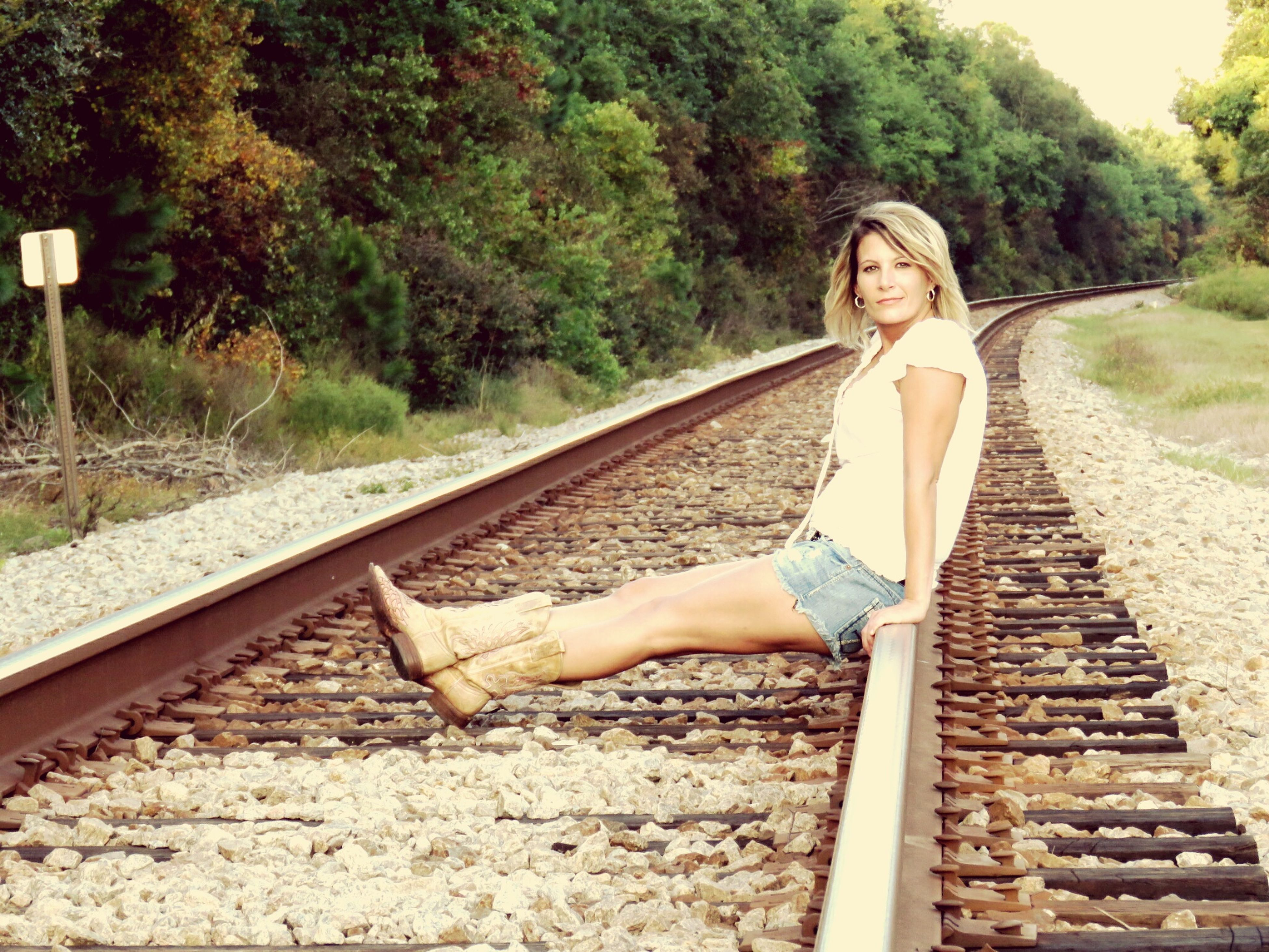 railroad track, transportation, full length, young women, casual clothing, young adult, leisure activity, relaxation, lifestyles, person, travel, outdoors, day, summer, looking at camera, nature, long hair, carefree, vacations, the way forward, diminishing perspective