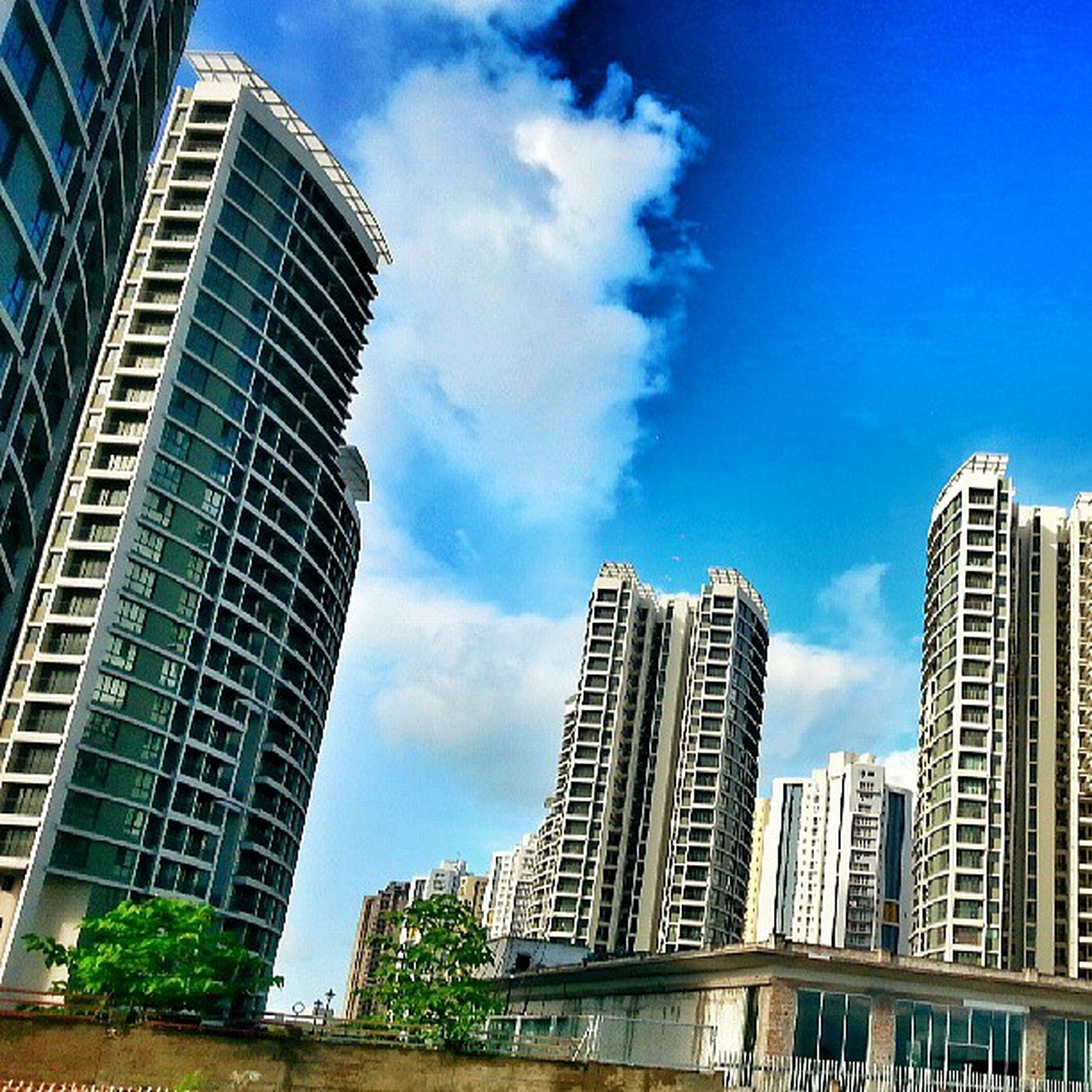 building exterior, architecture, built structure, city, modern, low angle view, skyscraper, office building, sky, blue, tall - high, building, tower, cloud - sky, cloud, glass - material, day, city life, financial district, outdoors