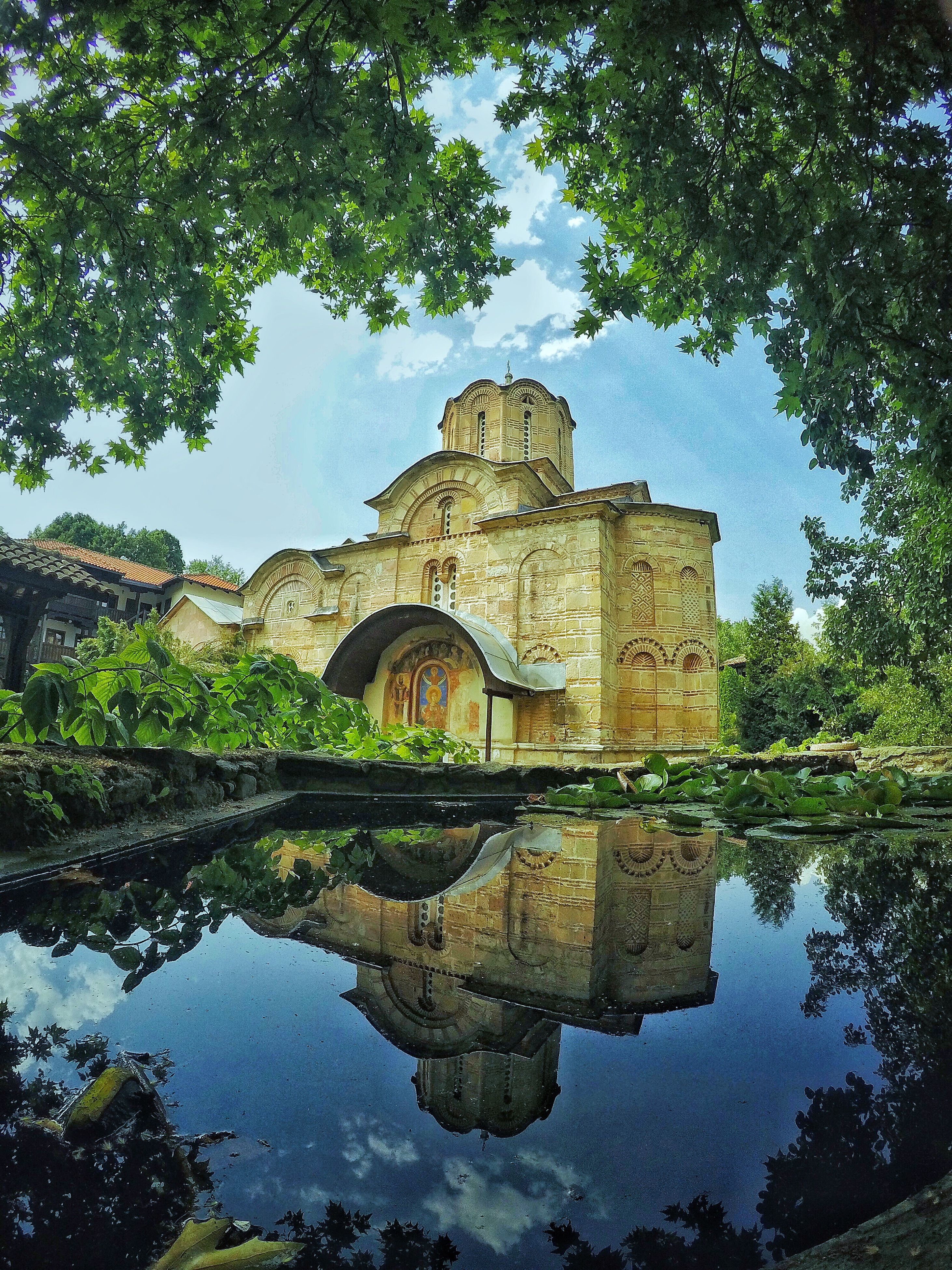 reflection, water, religion, architecture, tree, built structure, history, spirituality, place of worship, day, no people, outdoors, building exterior, sky, nature