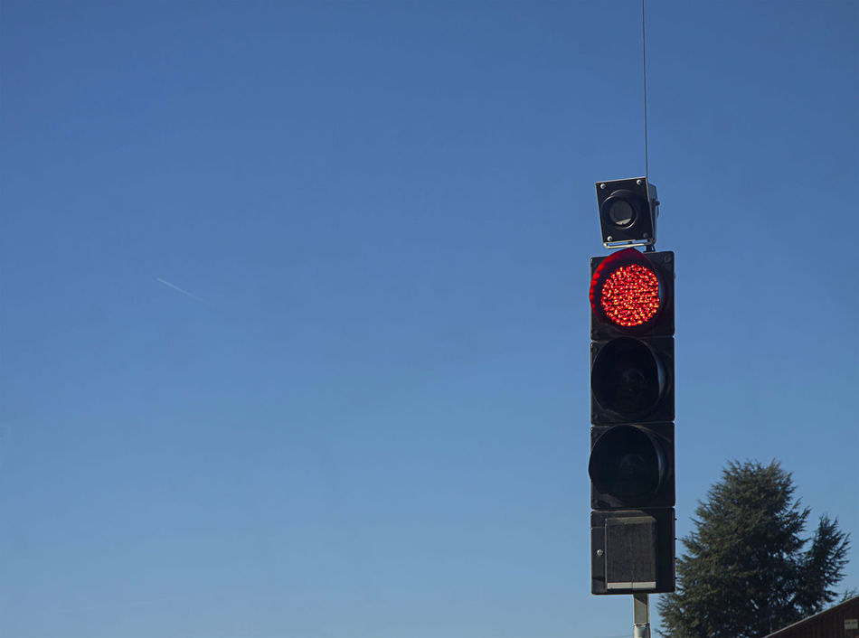 Semaphore with red light lit to regulate traffic at road crossing, blue sky background Abstract Control Crossroads Crosswalk Direction Forbidden Guidance Intersection Lamp Regulations Safety Semaphore Signage Stop Traffic Traffic Lights Transportation Urban