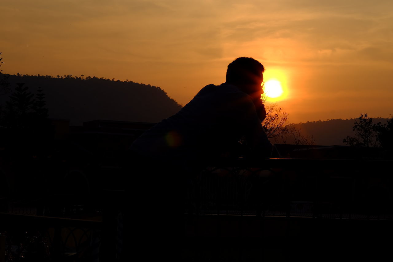 sunset, silhouette, one person, sky, real people, nature, outdoors, men, tree, sitting, beauty in nature, day, people