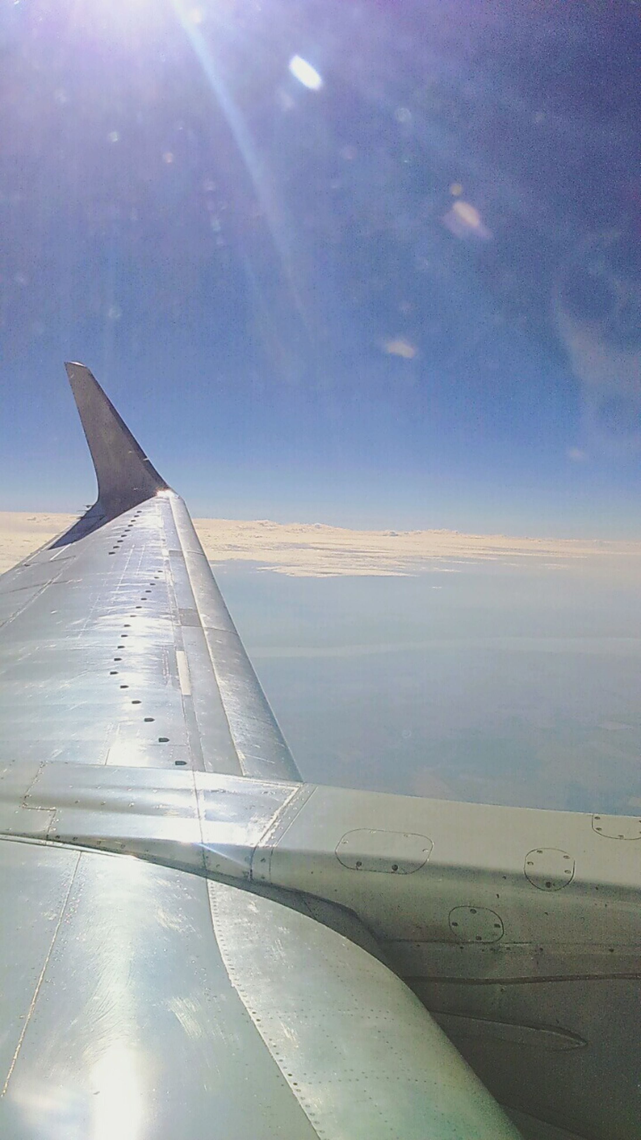 airplane, aircraft wing, air vehicle, flying, transportation, mode of transport, part of, sky, cropped, aerial view, mid-air, travel, cloud - sky, journey, airplane wing, on the move, nature, blue, beauty in nature, scenics