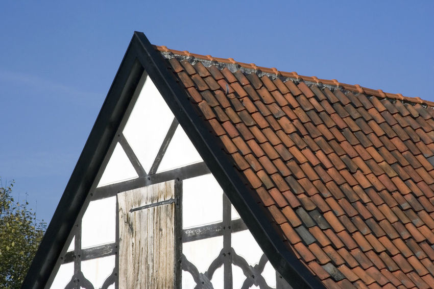 gable of a half-timbered house in black and white with red tiles - in a traditional german village Ancient Architecture Building Exterior Built Structure Clear Sky Close-up Cottage Façade Gable Germany Hagen Half-timbered High Section Home House Low Angle View No People NRW Old Old Buildings Residential Building Roof Roof Tile Tradition Vintage