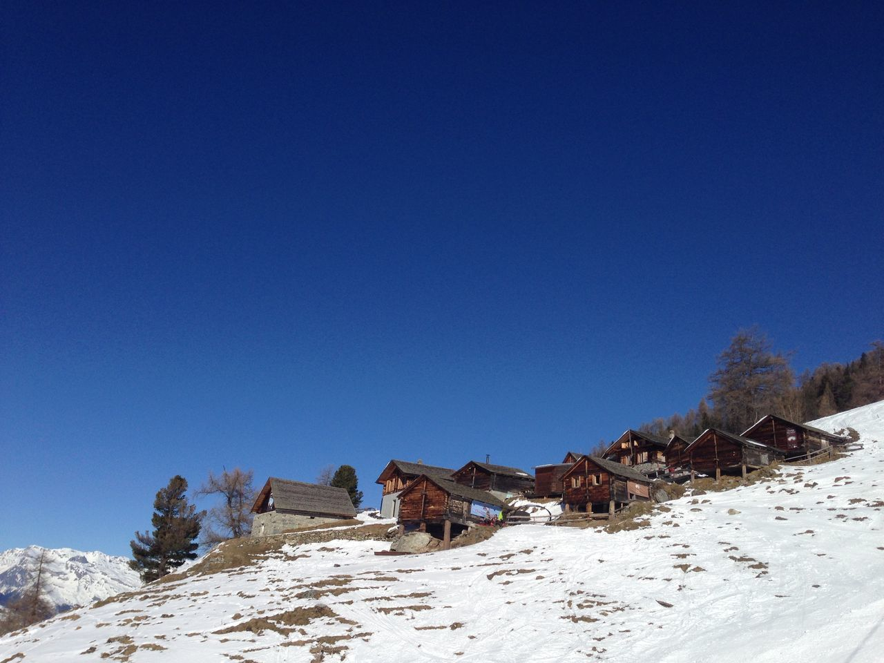 Houses On Snow Covered Field By Mountains Against Clear Blue Sky