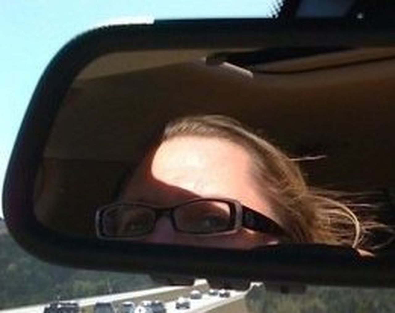 sunglasses, reflection, one person, car, portrait, headshot, people, driving, human body part, one woman only, adult, young adult, only women, adults only, day, looking at camera, sunlight, vehicle mirror, close-up, human eye, eyesight, beautiful woman, one young woman only, young women, outdoors, sky