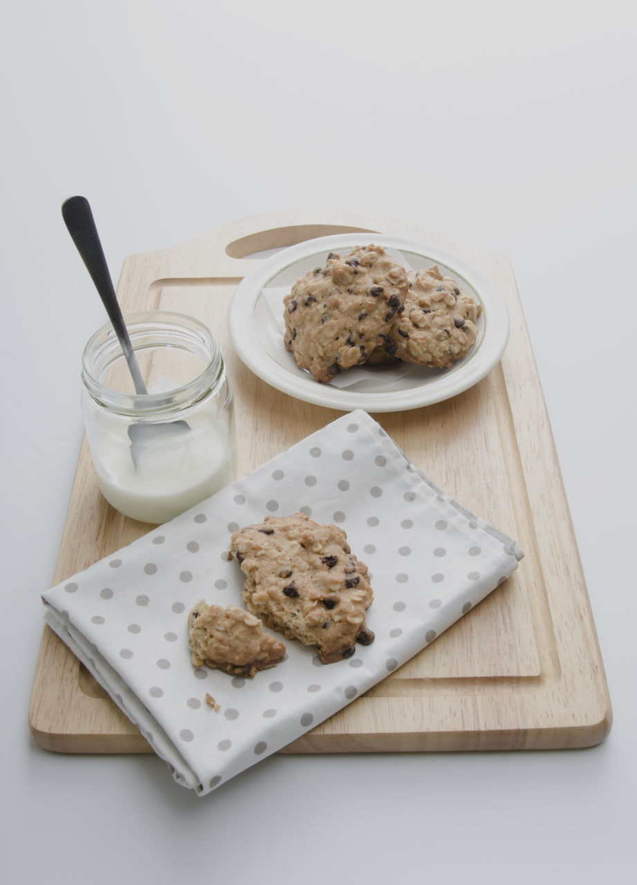 High Angle View Of Cookies With Milk Jar On Cutting Board Against White Background