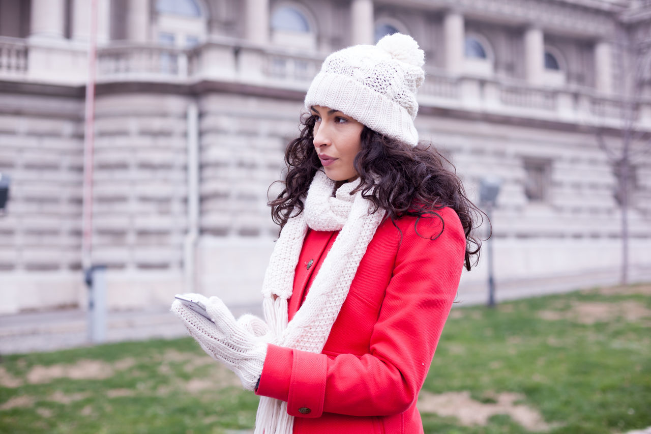 Young Woman Holding Smart Phone Looking Away While Standing On City Street