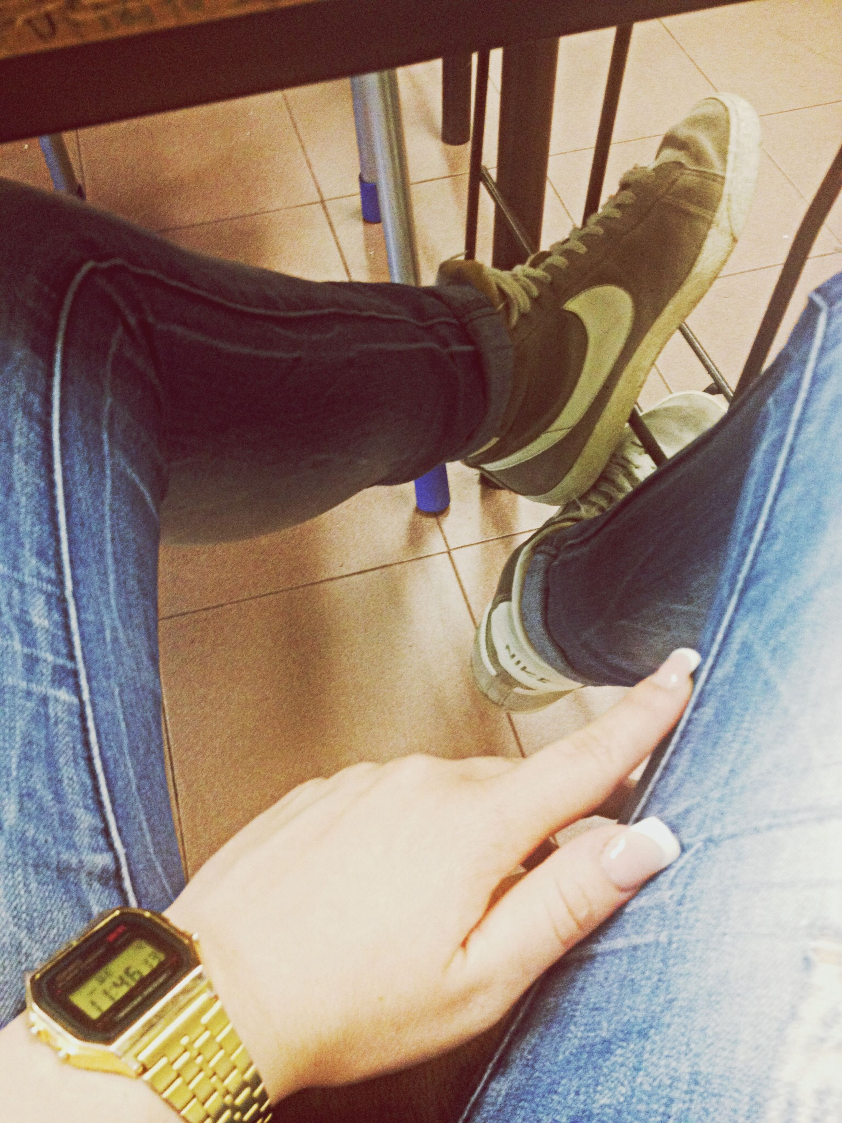 low section, person, indoors, shoe, lifestyles, men, personal perspective, jeans, sitting, footwear, human foot, leisure activity, part of, legs crossed at ankle, casual clothing, standing, fashion