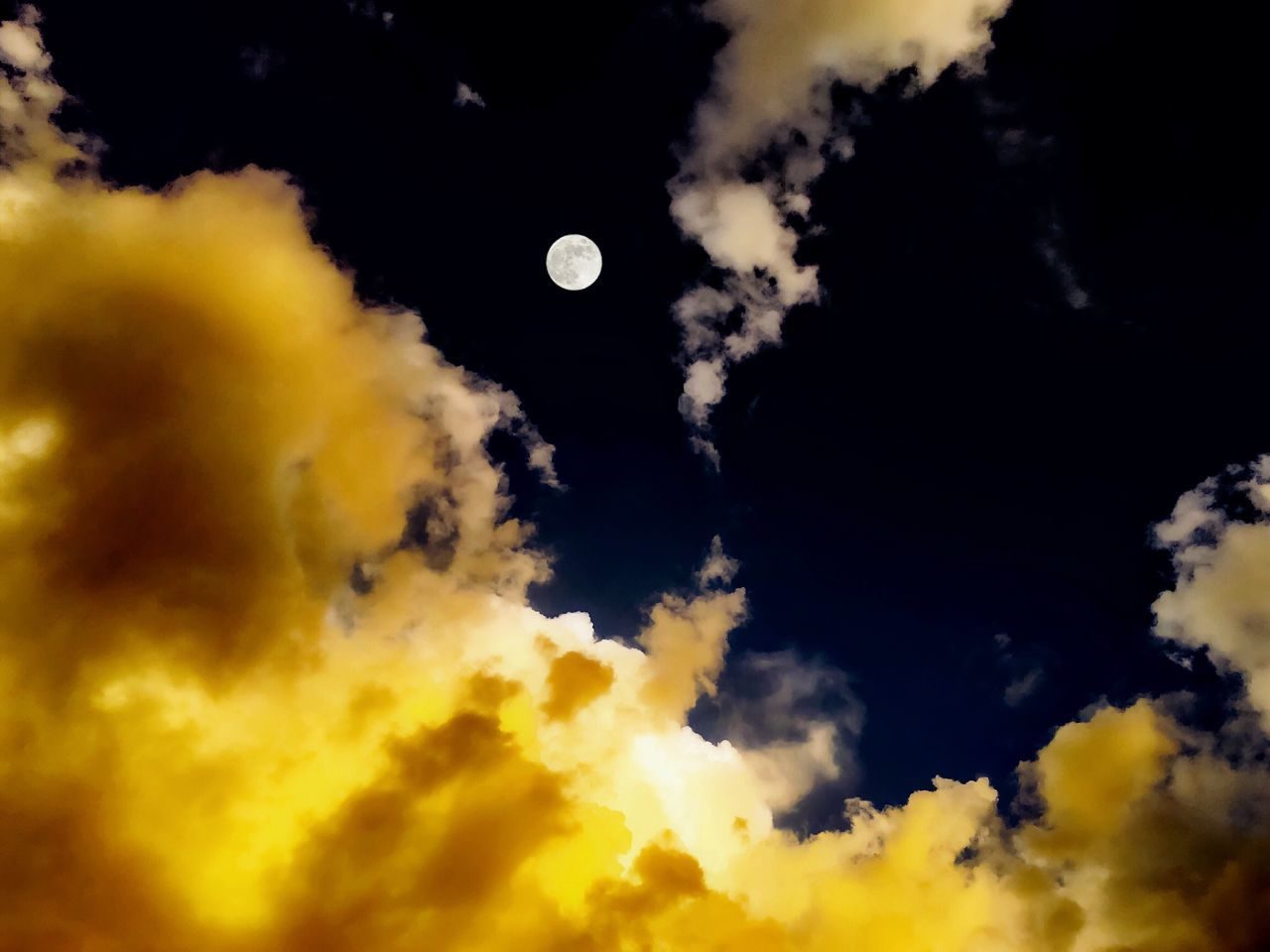 LOW ANGLE VIEW OF MOON AGAINST CLOUDY SKY