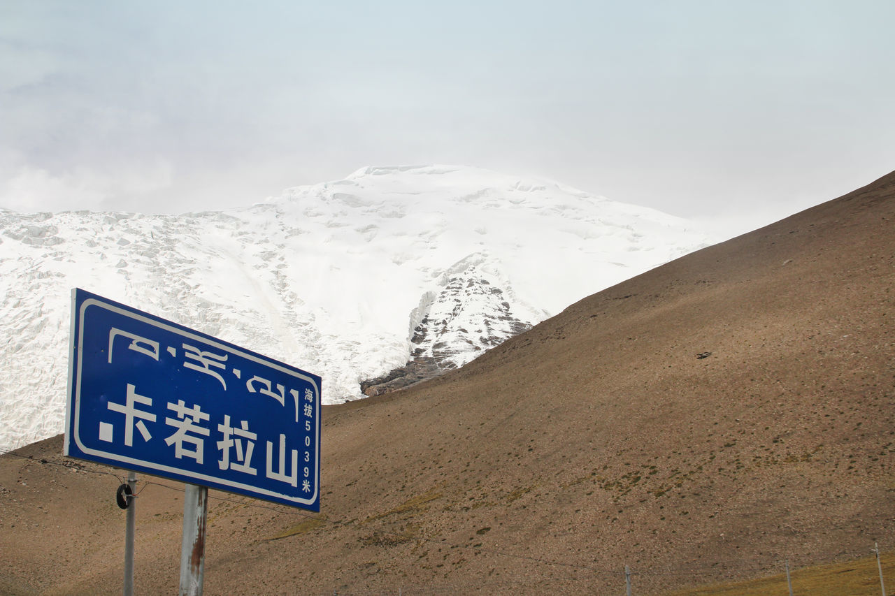 text, communication, mountain, no people, nature, sky, tranquility, day, beauty in nature, scenics, outdoors, snow, landscape, road sign, cold temperature, close-up