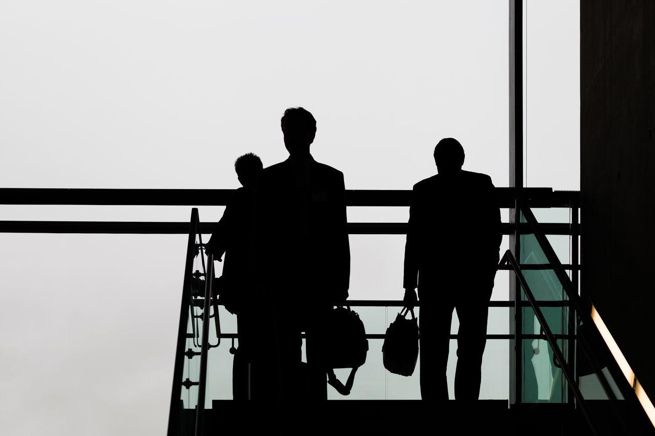 Silhouette Businessmen Walking On Steps Against Sky