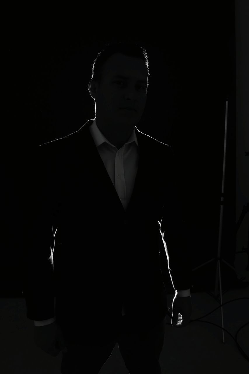 one person, real people, young adult, studio shot, standing, young men, men, lifestyles, black background, well-dressed, suit, indoors, day, people