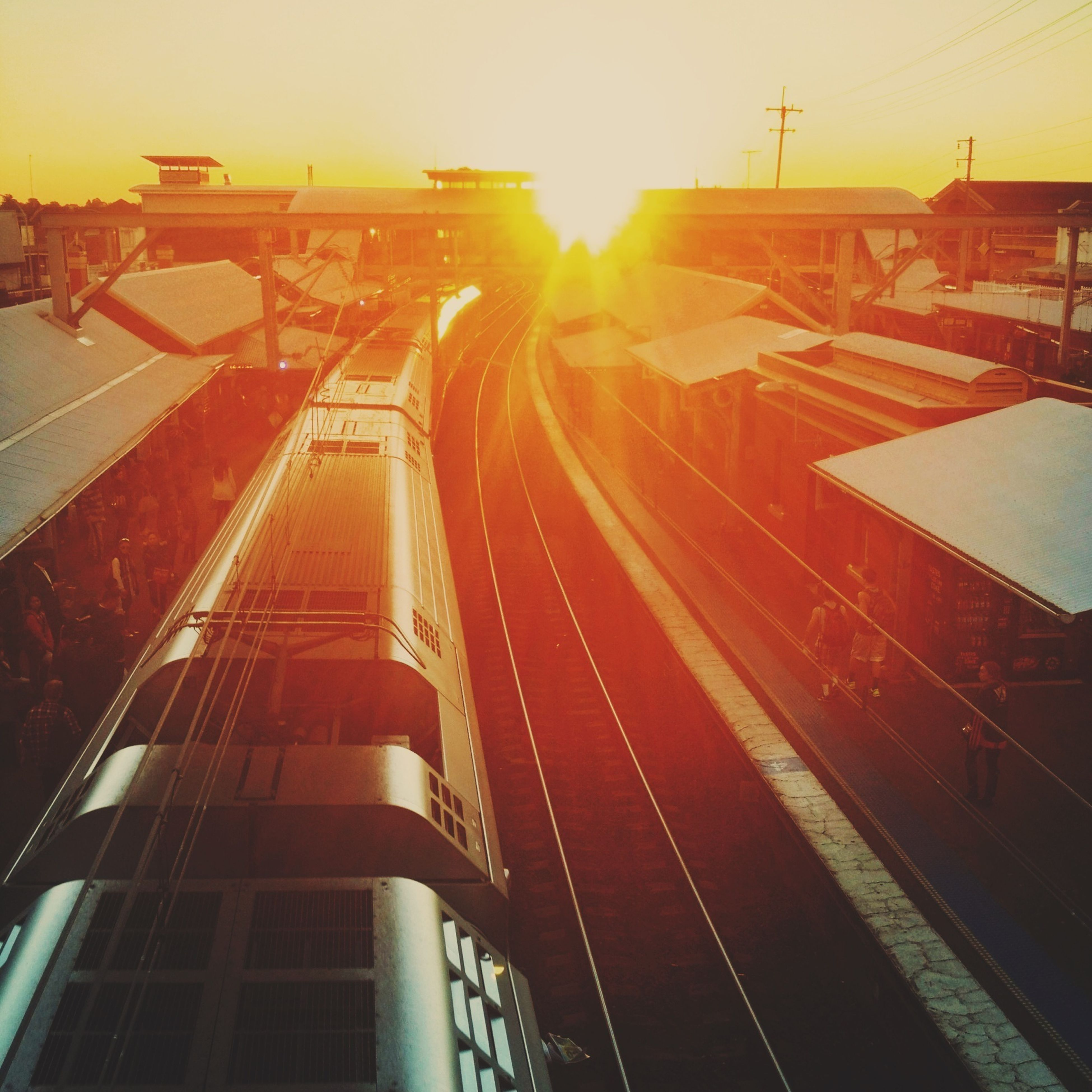 transportation, railroad track, architecture, building exterior, built structure, public transportation, rail transportation, city, mode of transport, sunset, railroad station, sunlight, high angle view, sun, railroad station platform, sky, lens flare, the way forward, outdoors, city life