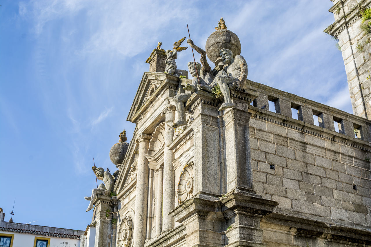 statue, human representation, sculpture, low angle view, architecture, art and craft, building exterior, female likeness, travel destinations, built structure, sky, outdoors, cloud - sky, day, history, no people