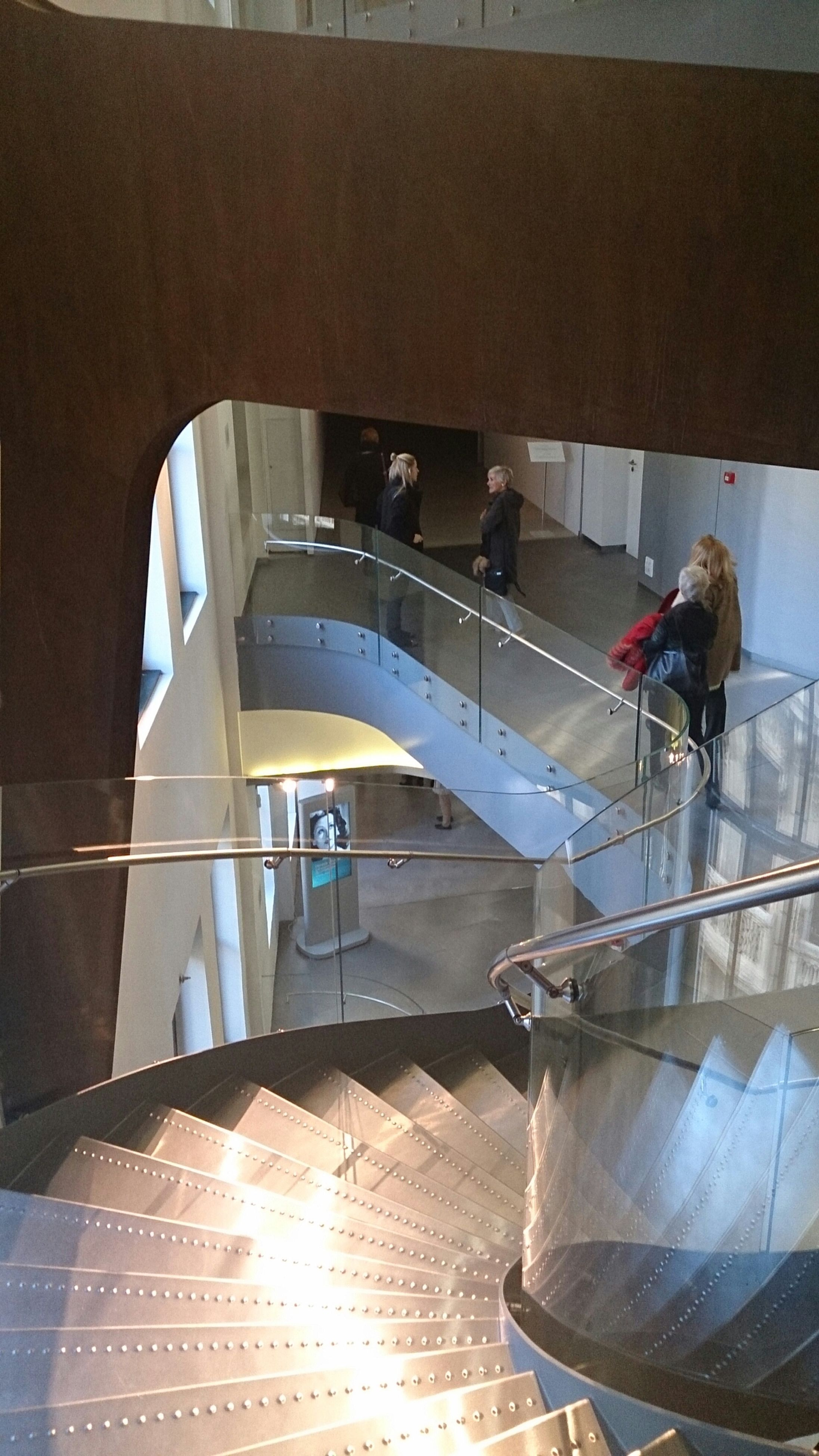 indoors, steps, men, steps and staircases, high angle view, architecture, built structure, staircase, lifestyles, railing, person, full length, leisure activity, sitting, sunlight, rear view, transportation, reflection