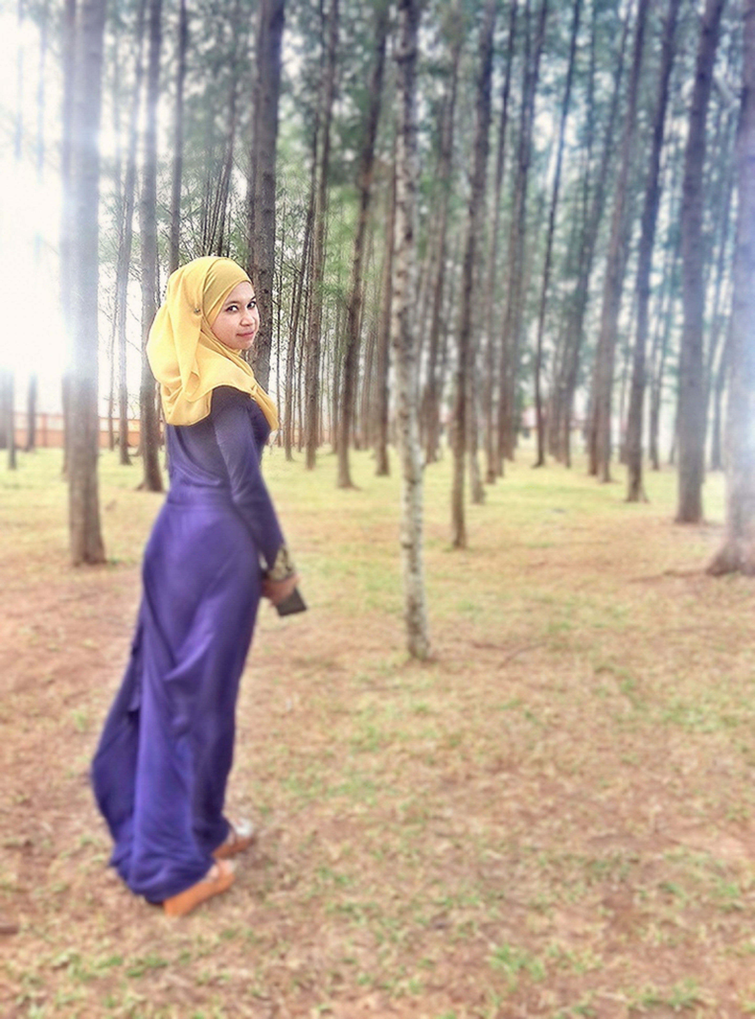 tree, lifestyles, casual clothing, leisure activity, forest, rear view, standing, full length, tree trunk, woodland, warm clothing, focus on foreground, field, nature, day, tranquility, front view, grass