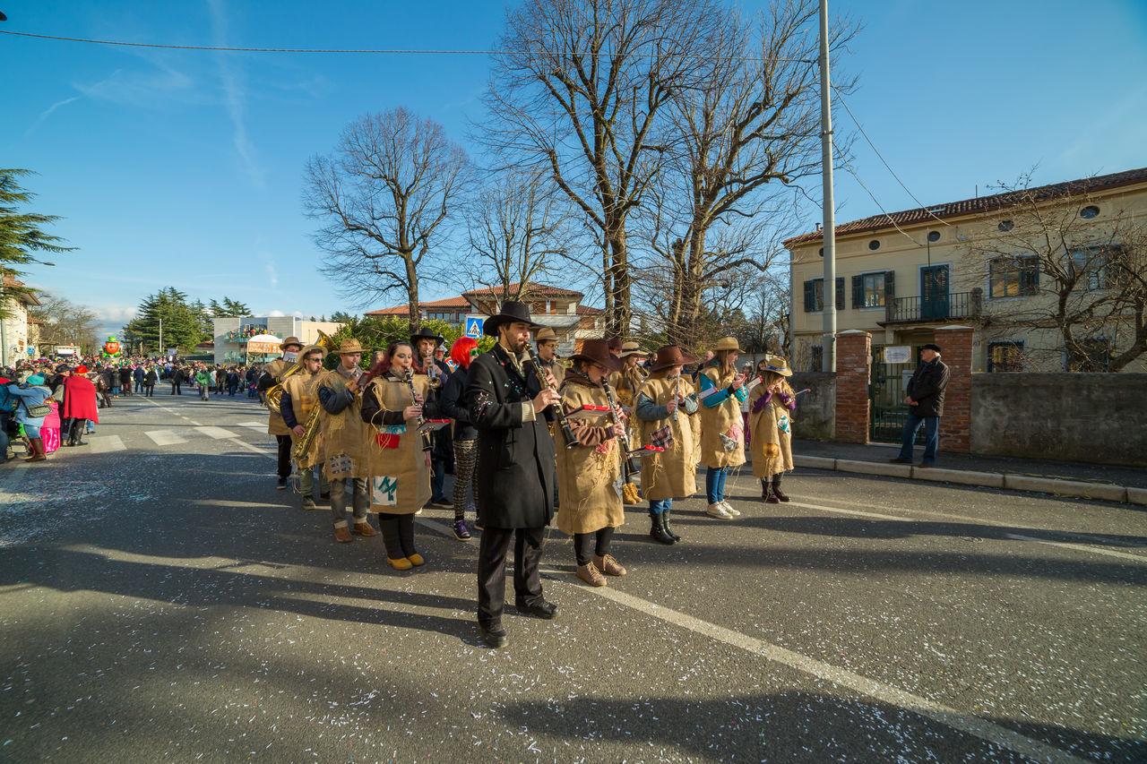 building exterior, built structure, architecture, street, large group of people, real people, bare tree, road, outdoors, day, walking, men, city, tree, sky, women, clear sky, people