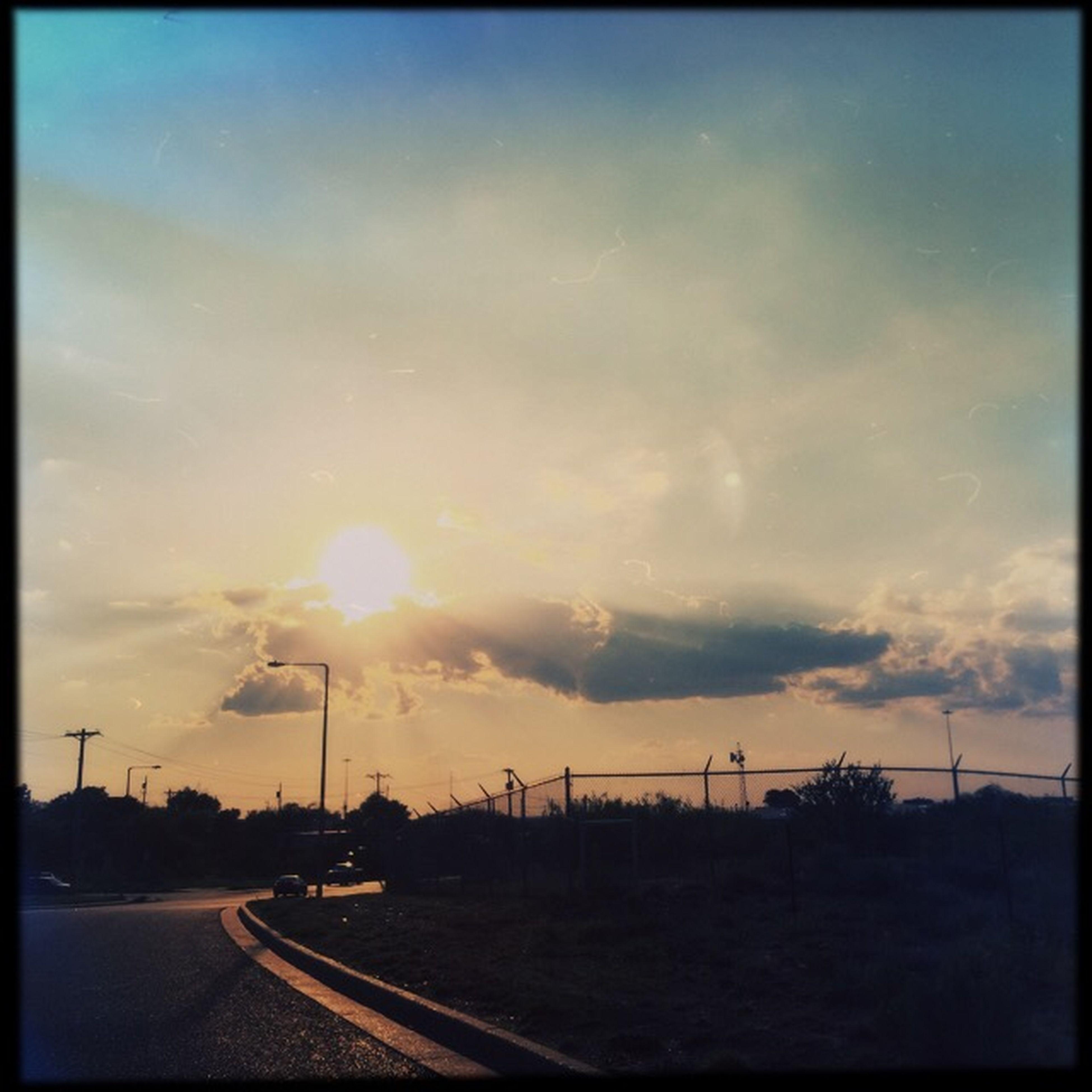 sunset, transportation, sky, transfer print, road, cloud - sky, landscape, auto post production filter, sun, car, orange color, field, cloud, scenics, mode of transport, nature, cloudy, land vehicle, beauty in nature, sunlight