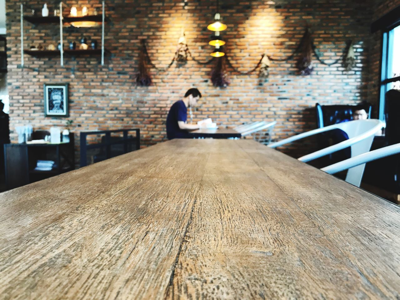table, indoors, real people, wood - material, sitting, one person, chair, desk, cafe, illuminated, bar - drink establishment, lifestyles, women, day, architecture, people
