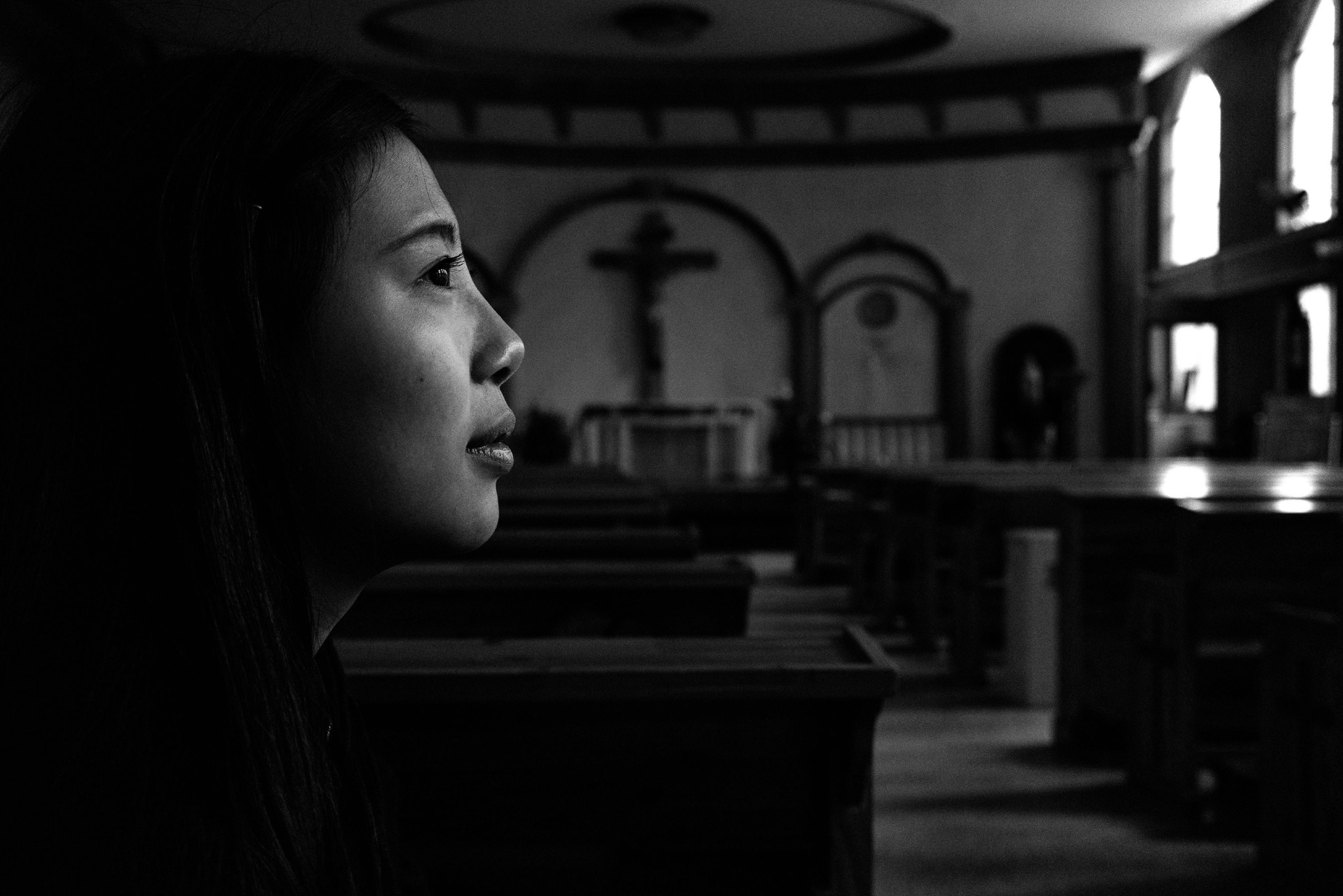indoors, architecture, lifestyles, headshot, focus on foreground, built structure, contemplation, spirituality, religion, front view, person, place of worship, young adult, looking at camera, close-up, portrait, leisure activity