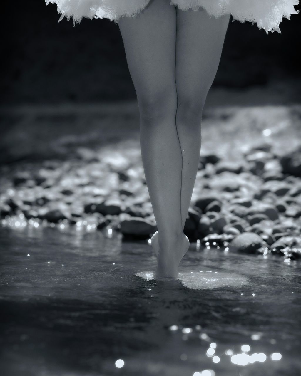 Low Section Of Woman Standing In Water