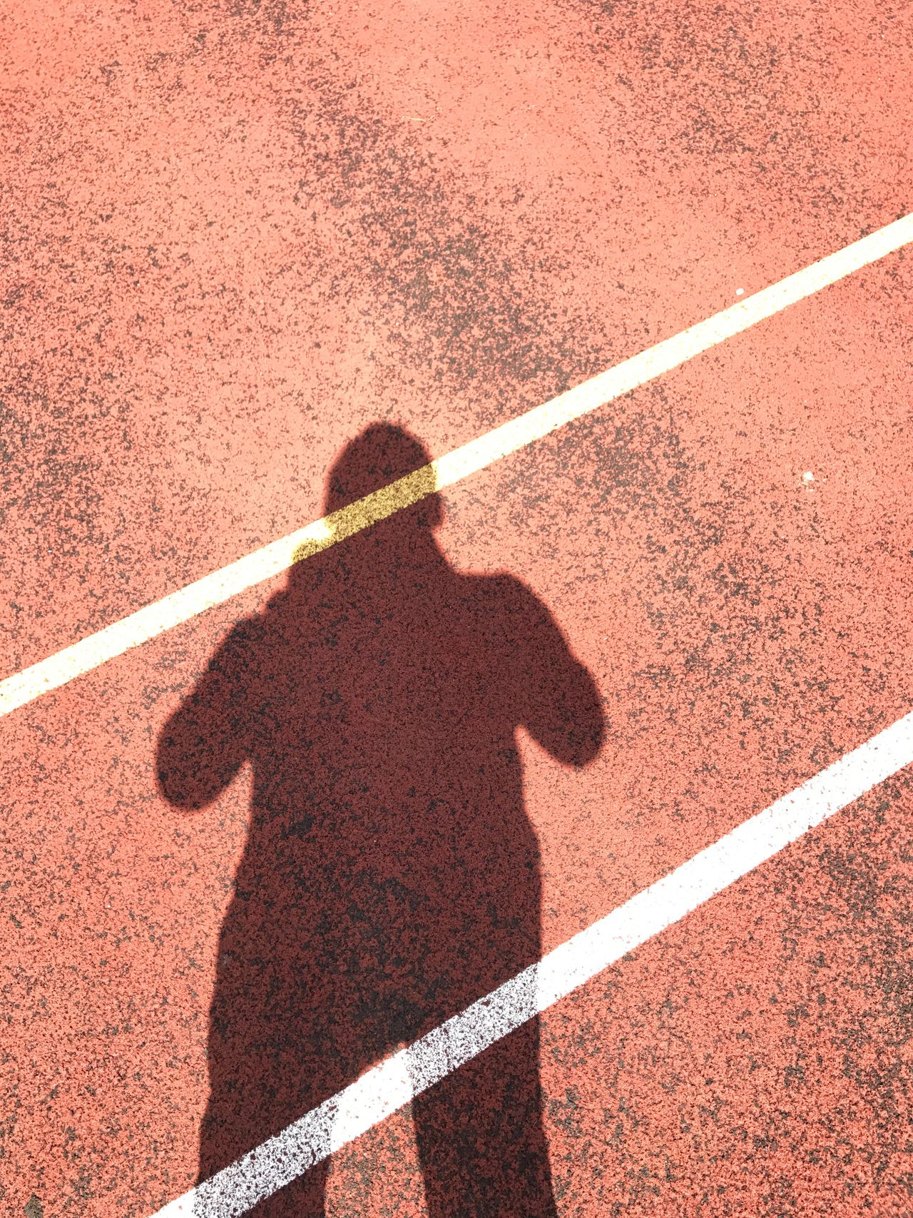Shadow Sport Focus On Shadow Running Track Track And Field One Person Sunlight Red Outdoors High Angle View Tennis Dividing Line Leisure Activity Court Sports Track Human Body Part Day Starting Line Competitive Sport Track And Field Athlete