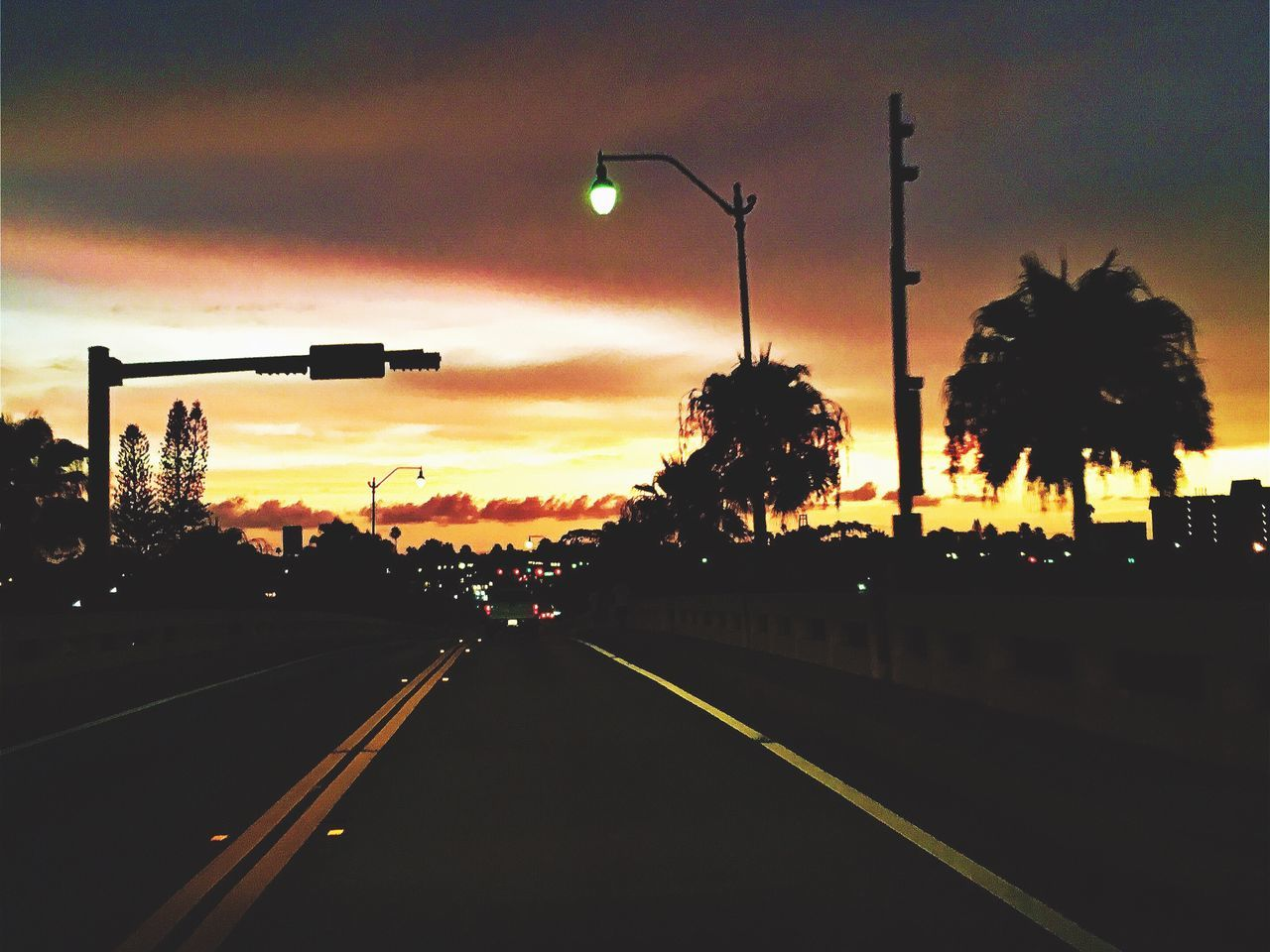 transportation, road, sunset, street light, car, illuminated, tree, sky, the way forward, stoplight, street, mode of transport, outdoors, silhouette, land vehicle, no people, city, road sign, architecture, day, nature