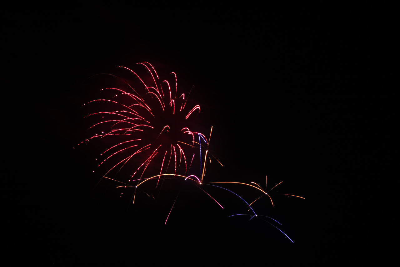 night, firework display, firework - man made object, celebration, exploding, long exposure, arts culture and entertainment, copy space, motion, illuminated, event, low angle view, no people, blurred motion, firework, red, multi colored, clear sky, outdoors, sky