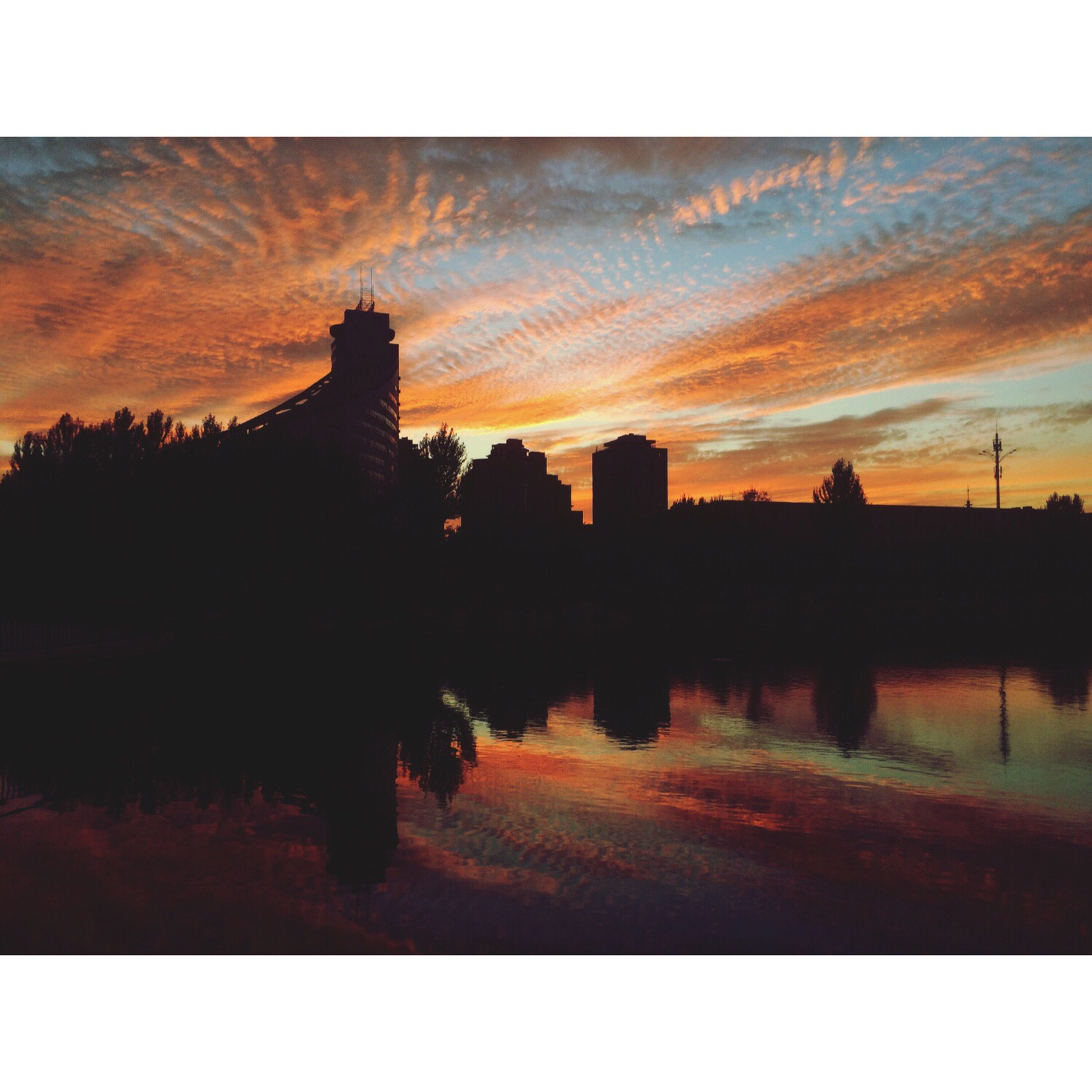 sunset, silhouette, water, architecture, lake, built structure, building exterior, sky, auto post production filter, reflection, orange color, cloud - sky, scenics, tranquility, tranquil scene, cloud, outdoors, growth, nature, beauty in nature, standing water, moody sky, dramatic sky, no people, cloudy