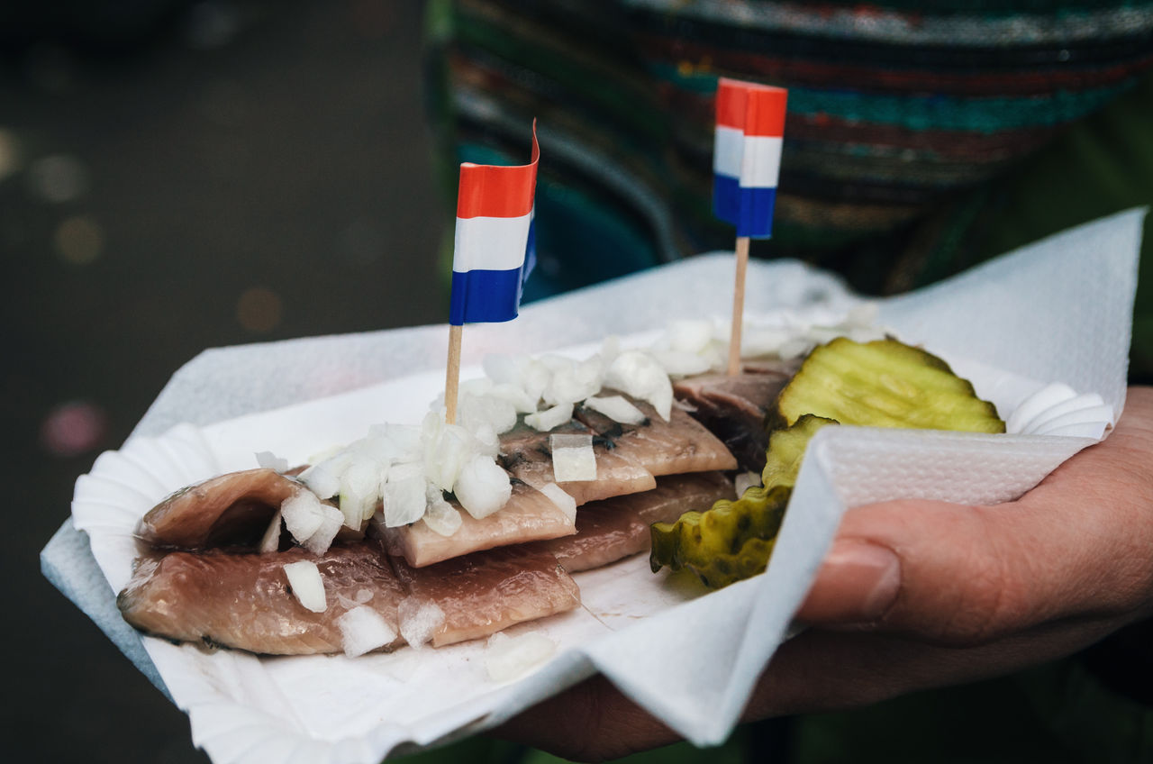 A hand holds a traditional Dutch delicacy of herring with gherkins and onions. Amsterdam Amsterdamcity Close-up Dutch Fast Food Fish Flag Food Food And Drink Freshness Herring Holland Human Hand Netherlands Ready-to-eat