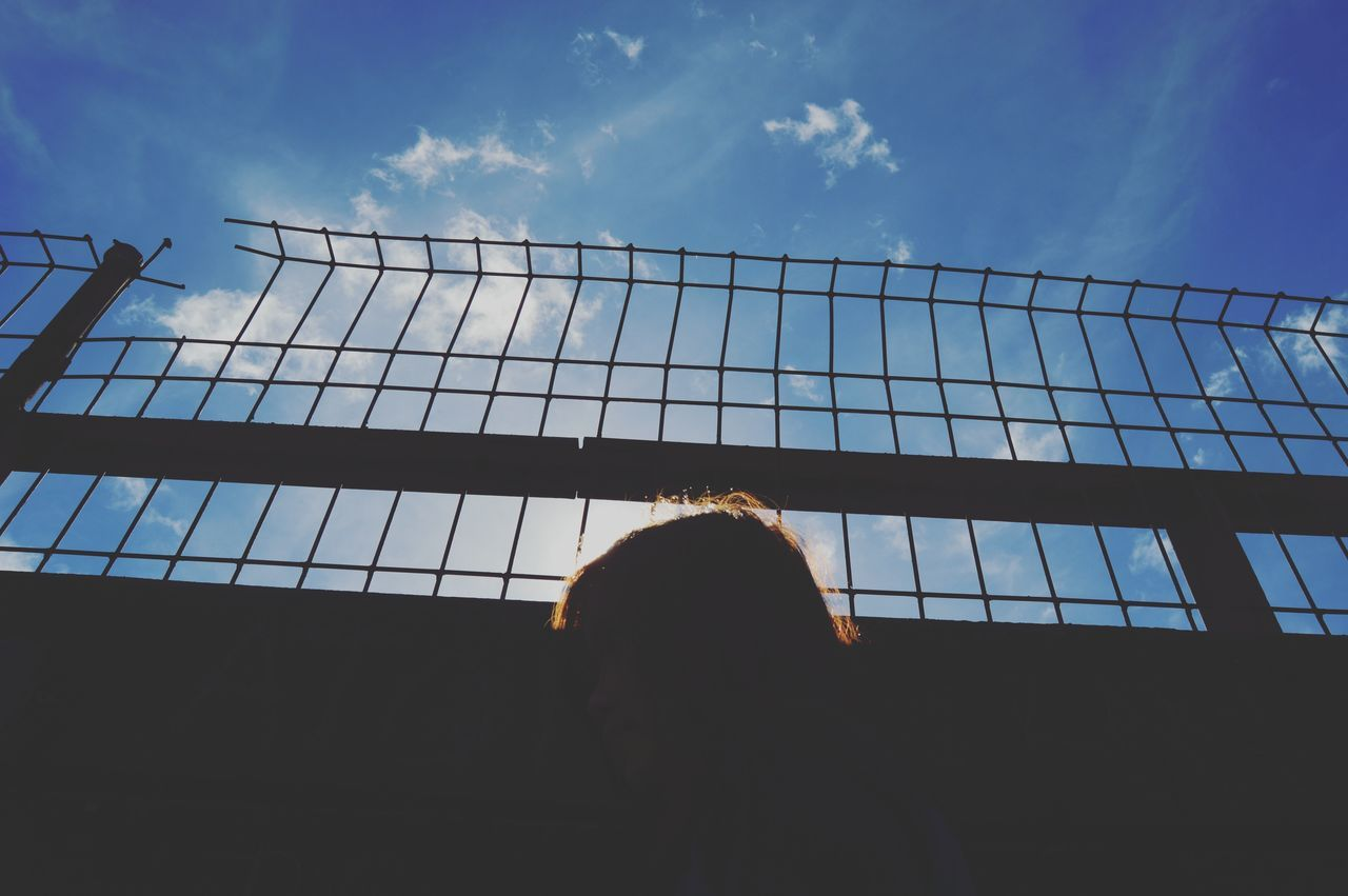 Low Angle View Of Person By Fence Against Blue Sky