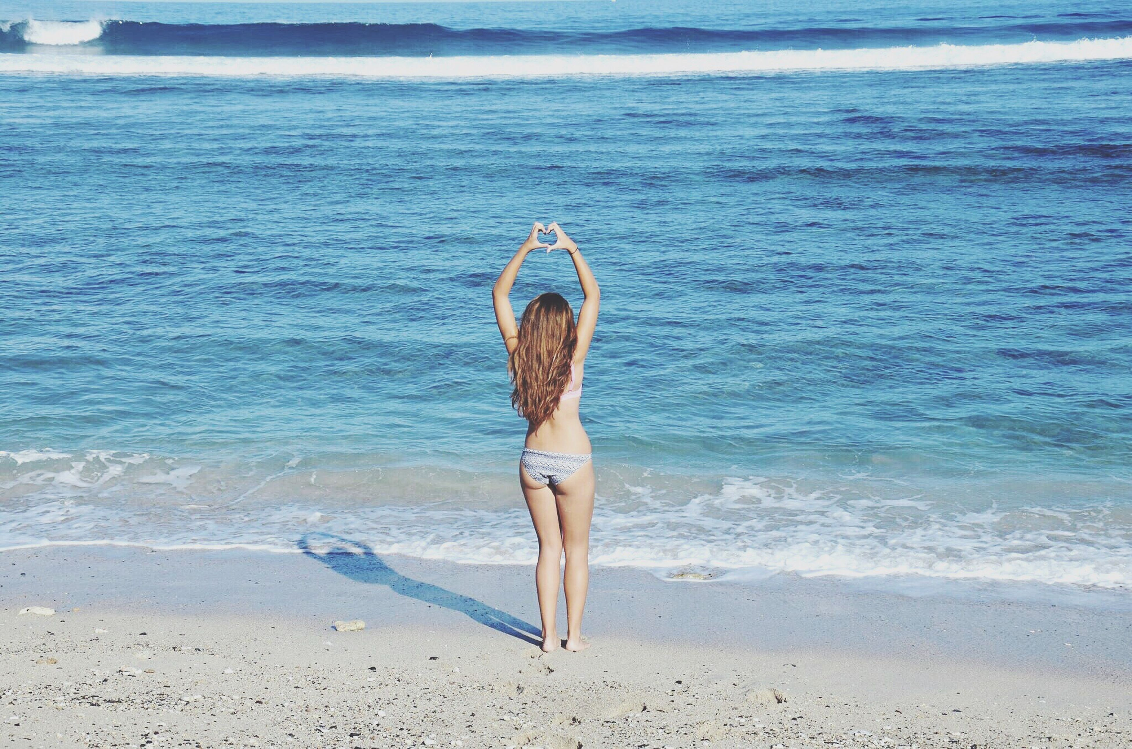 sea, water, beach, full length, lifestyles, leisure activity, young adult, standing, vacations, shore, young women, sand, casual clothing, rear view, tranquility, horizon over water, bikini, person