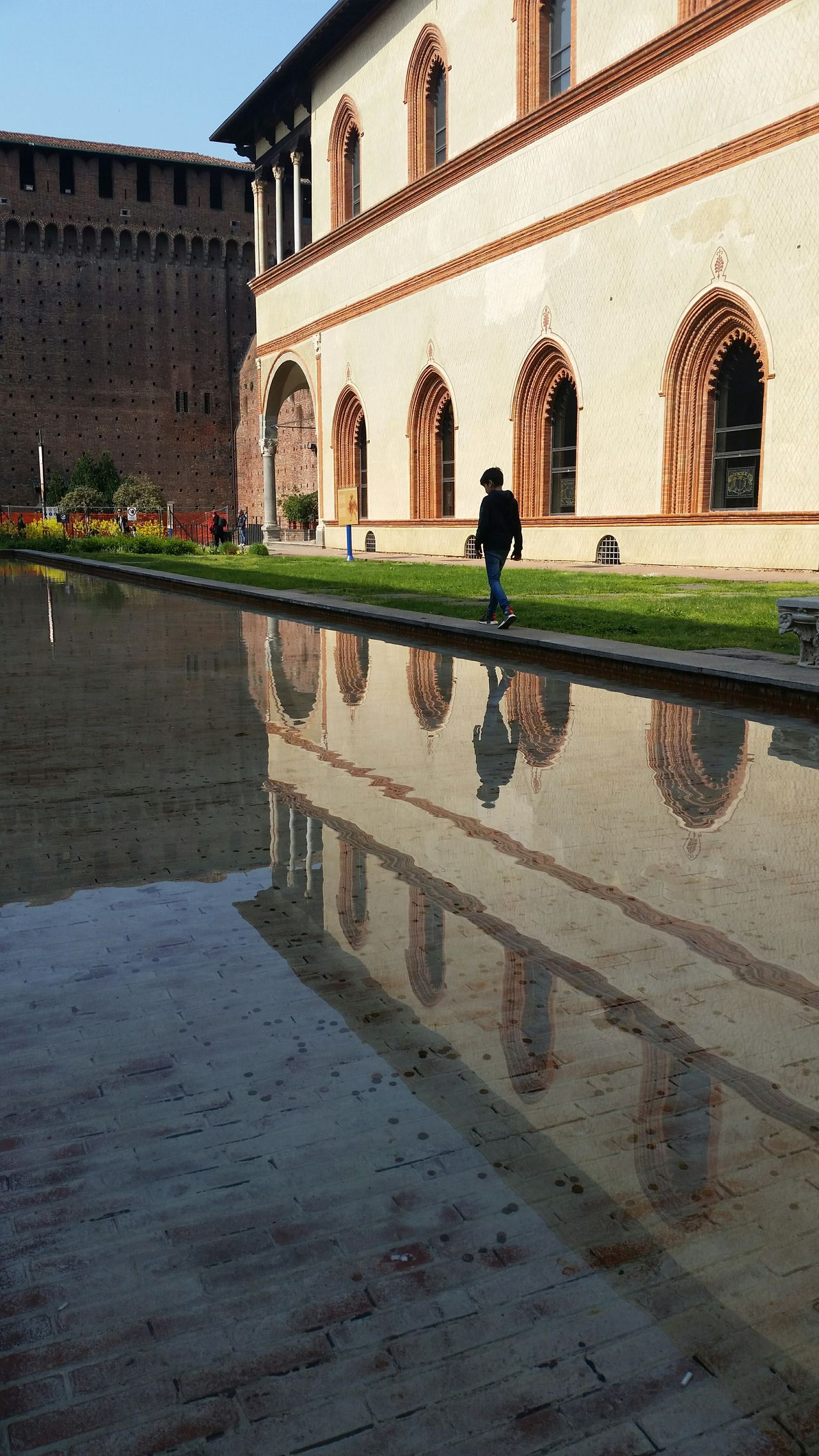 Boy reflected in a shallow pool inside Castello Sforzesco Architecture Reflection Travel Destinations Outdoors Water Day One Person Milan Milano Milan Italy Castle Castle Grounds Alone Boy Travel Photography Built Structure