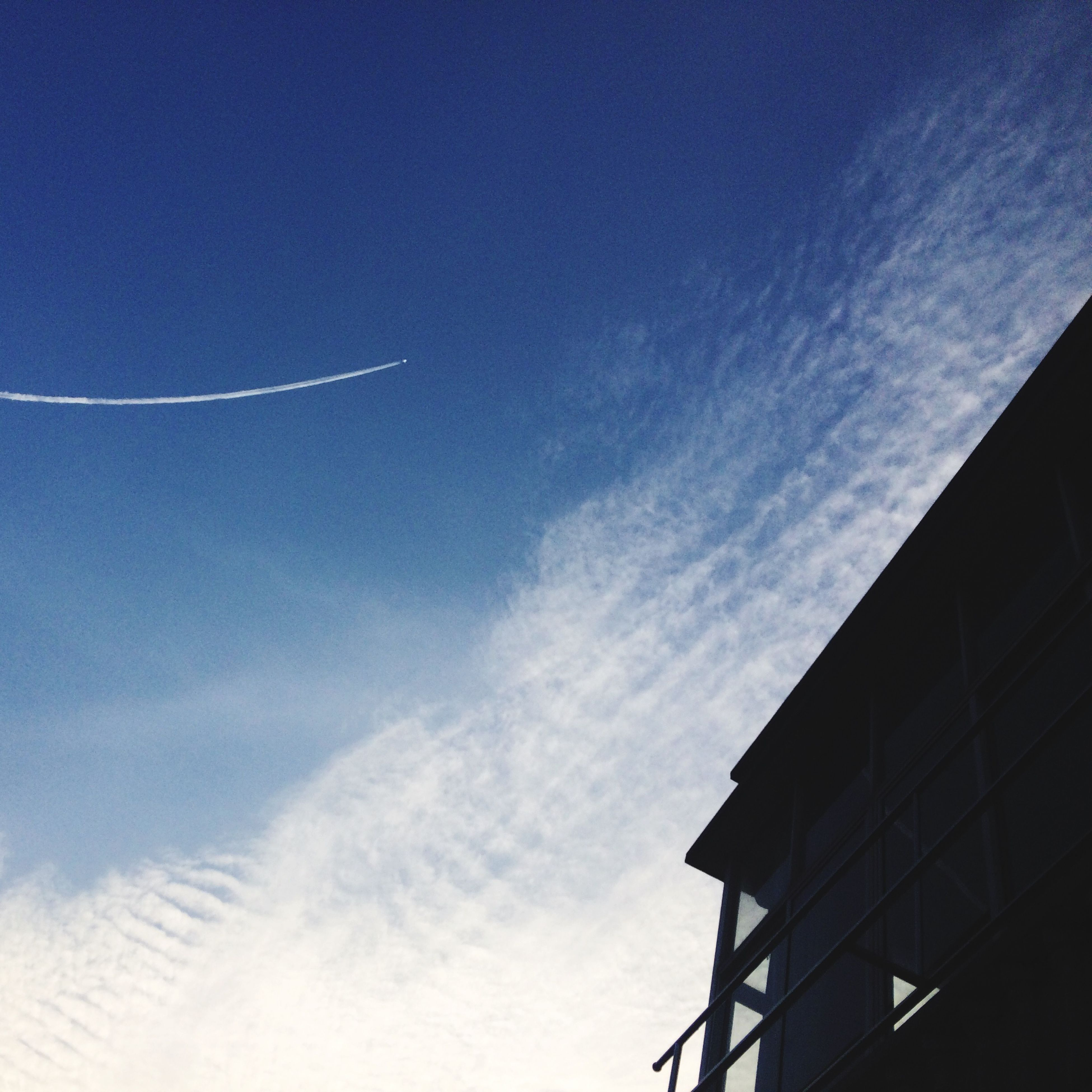 low angle view, building exterior, architecture, built structure, sky, blue, cloud - sky, vapor trail, outdoors, cloud, day, no people, nature, building, city, sunlight, window, high section, beauty in nature, scenics
