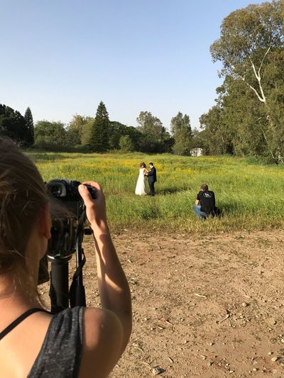 Real People Photography Themes Photographing Tree Field Leisure Activity Camera - Photographic Equipment Clear Sky Technology Rear View Lifestyles Day Digital Camera Leisure Grass Outdoors Nature Women Men Photographer Bride And Groom