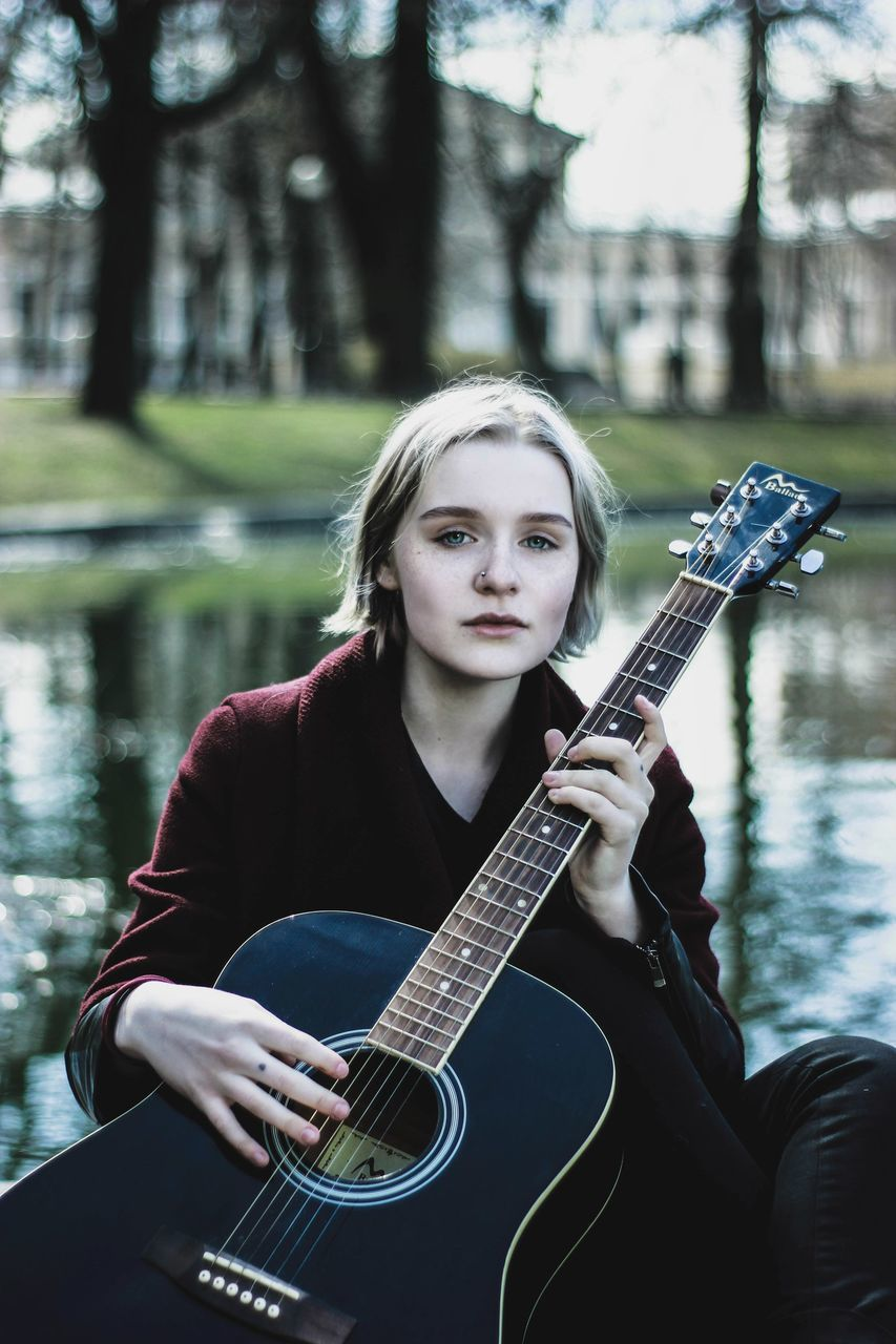 guitar, music, musical instrument, playing, front view, focus on foreground, leisure activity, outdoors, day, real people, one person, young adult, musician, plucking an instrument, lifestyles, performance, musical instrument string, nature, tree, people