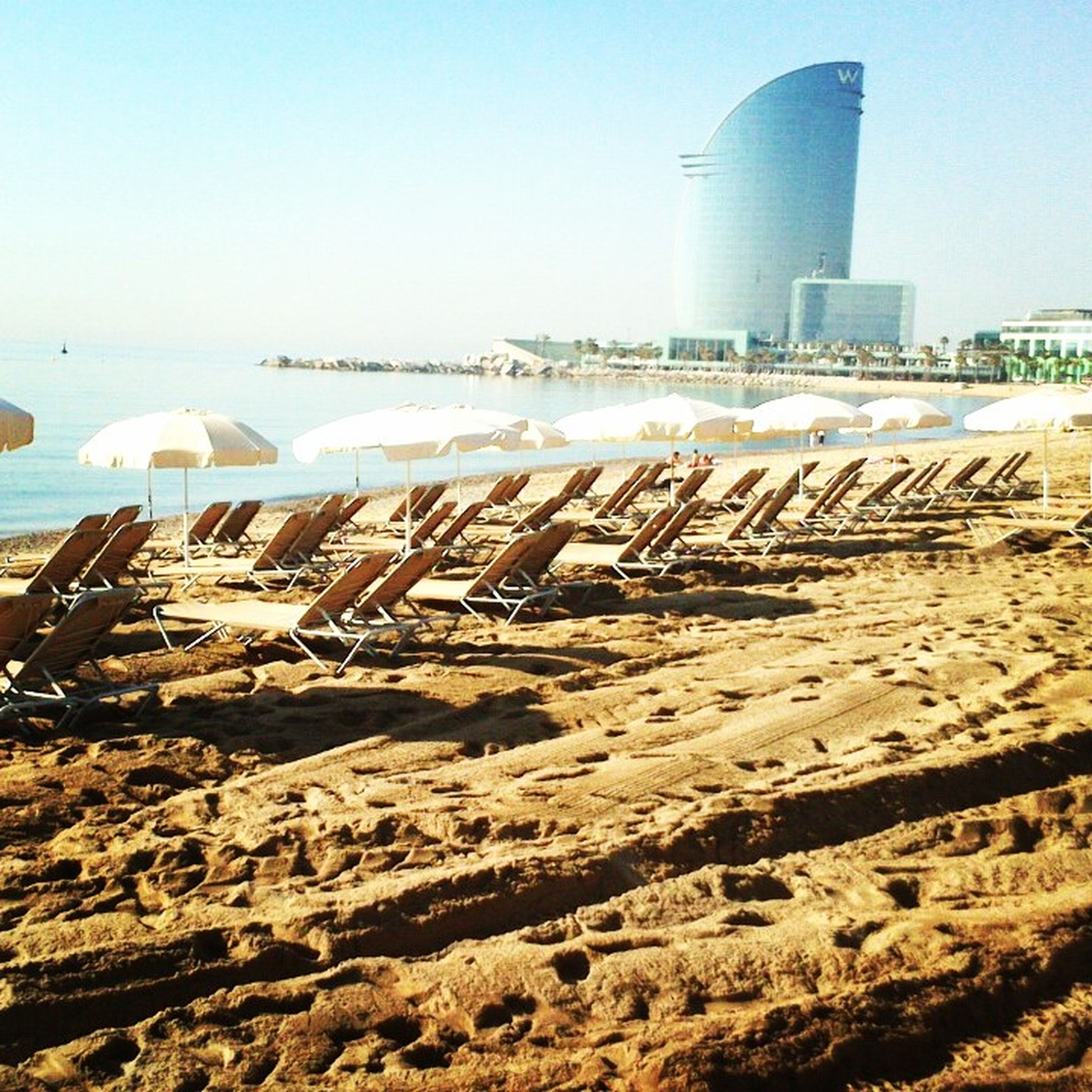 sand, beach, built structure, clear sky, architecture, building exterior, shore, sea, day, sunlight, water, outdoors, copy space, no people, travel destinations, city, incidental people, blue, industry, sky