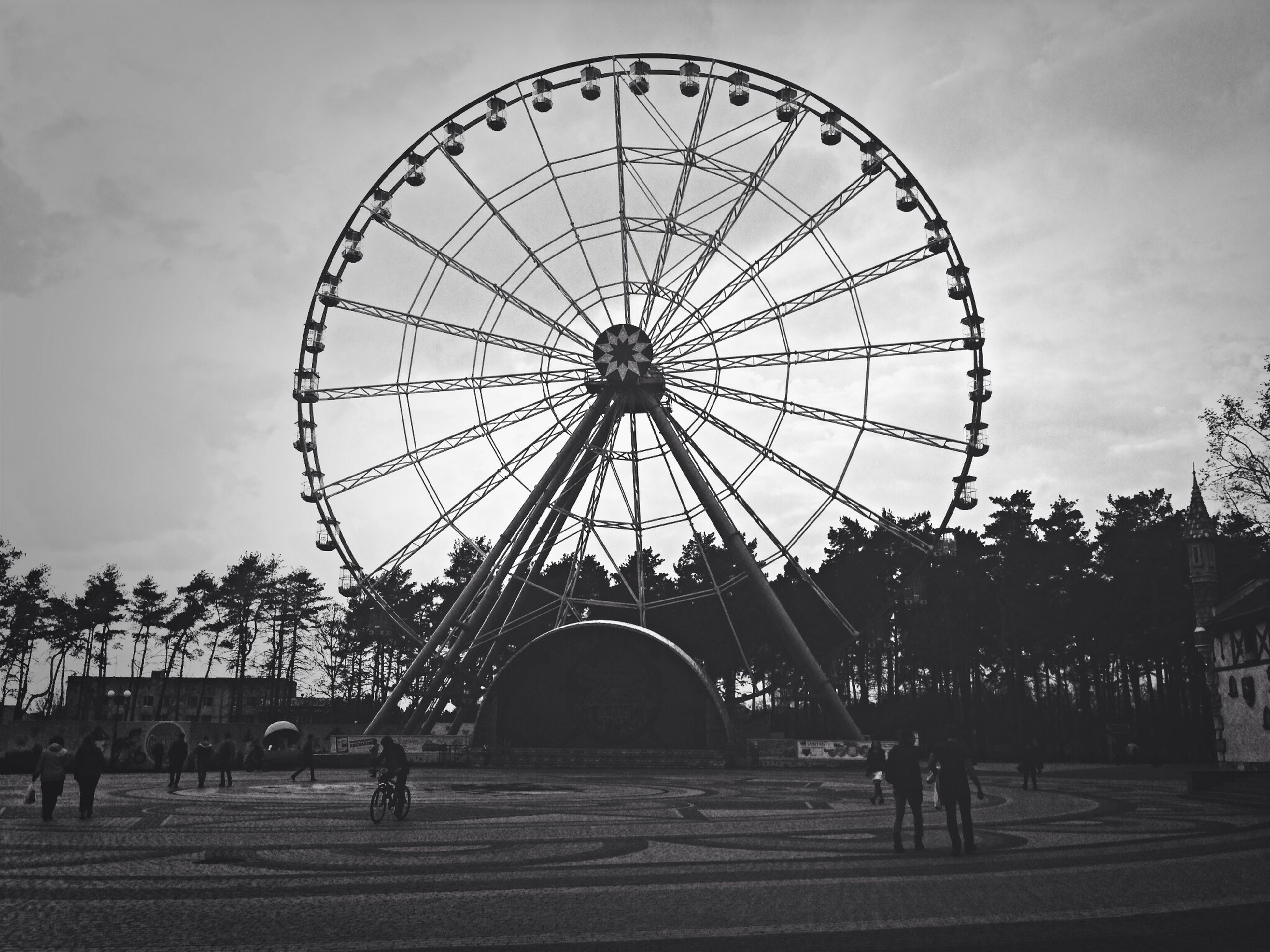 sky, ferris wheel, arts culture and entertainment, amusement park, amusement park ride, cloud - sky, low angle view, built structure, architecture, silhouette, cloudy, leisure activity, cloud, circle, tree, incidental people, outdoors, large group of people, day