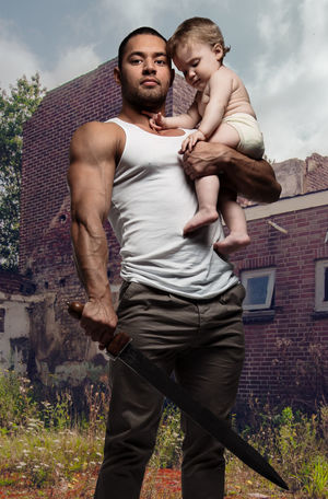 Father hugging a baby and holding a sword outdoors. Conceptual photo, parental protection. 1 Year Old Athletic Family Fatherhood Moments Hug Love Baby Girl Caucasian Child Childhood Conceptual Daughter Father Father And Daughter Little Girl Men Muscular Build Parent Parental Protection Parenthood Protection Sportive Sword Toddler  Two People