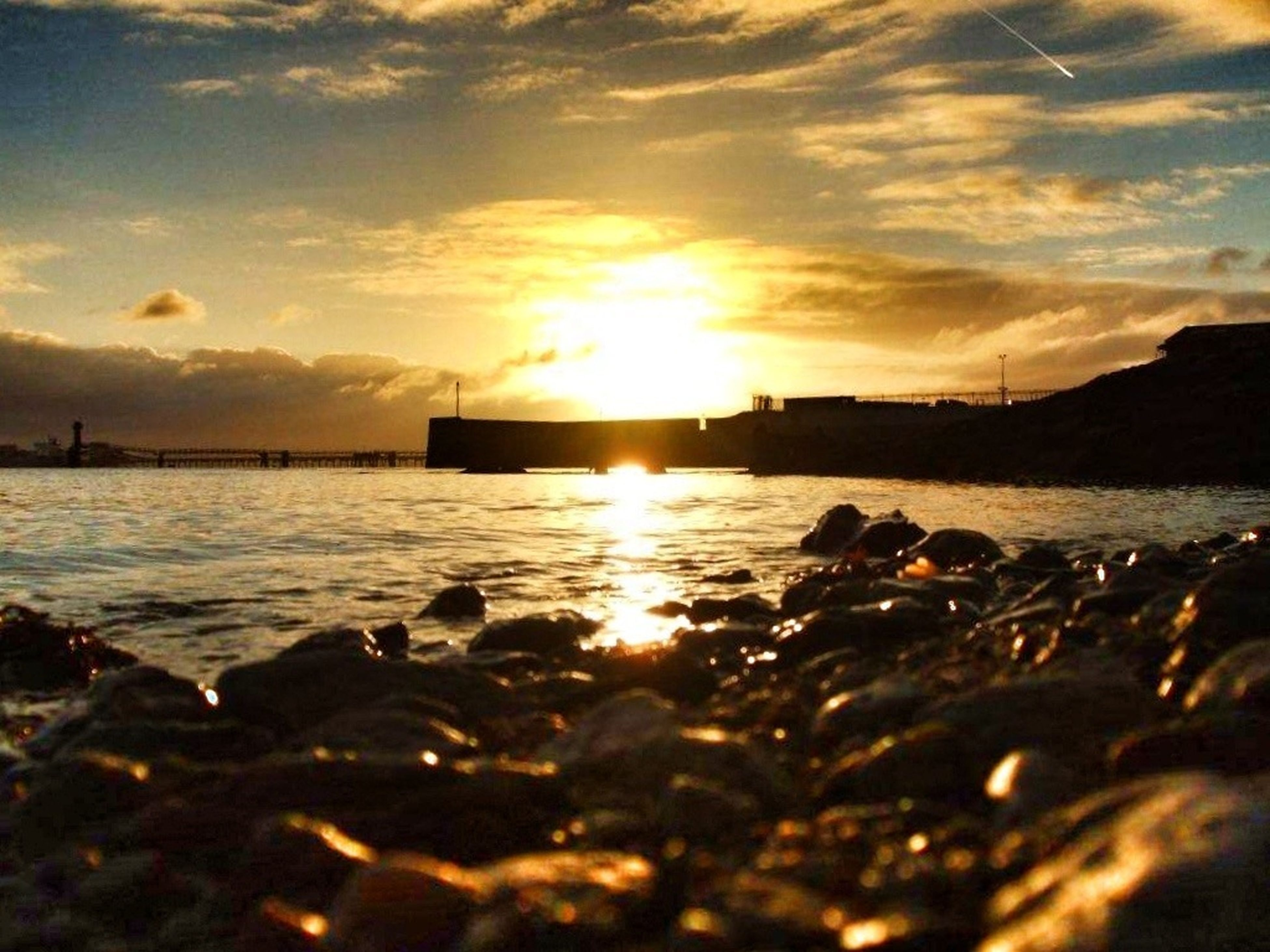 sunset, water, sky, sea, beach, scenics, tranquil scene, beauty in nature, shore, tranquility, cloud - sky, nature, sun, reflection, idyllic, rock - object, orange color, sunlight, silhouette, cloud