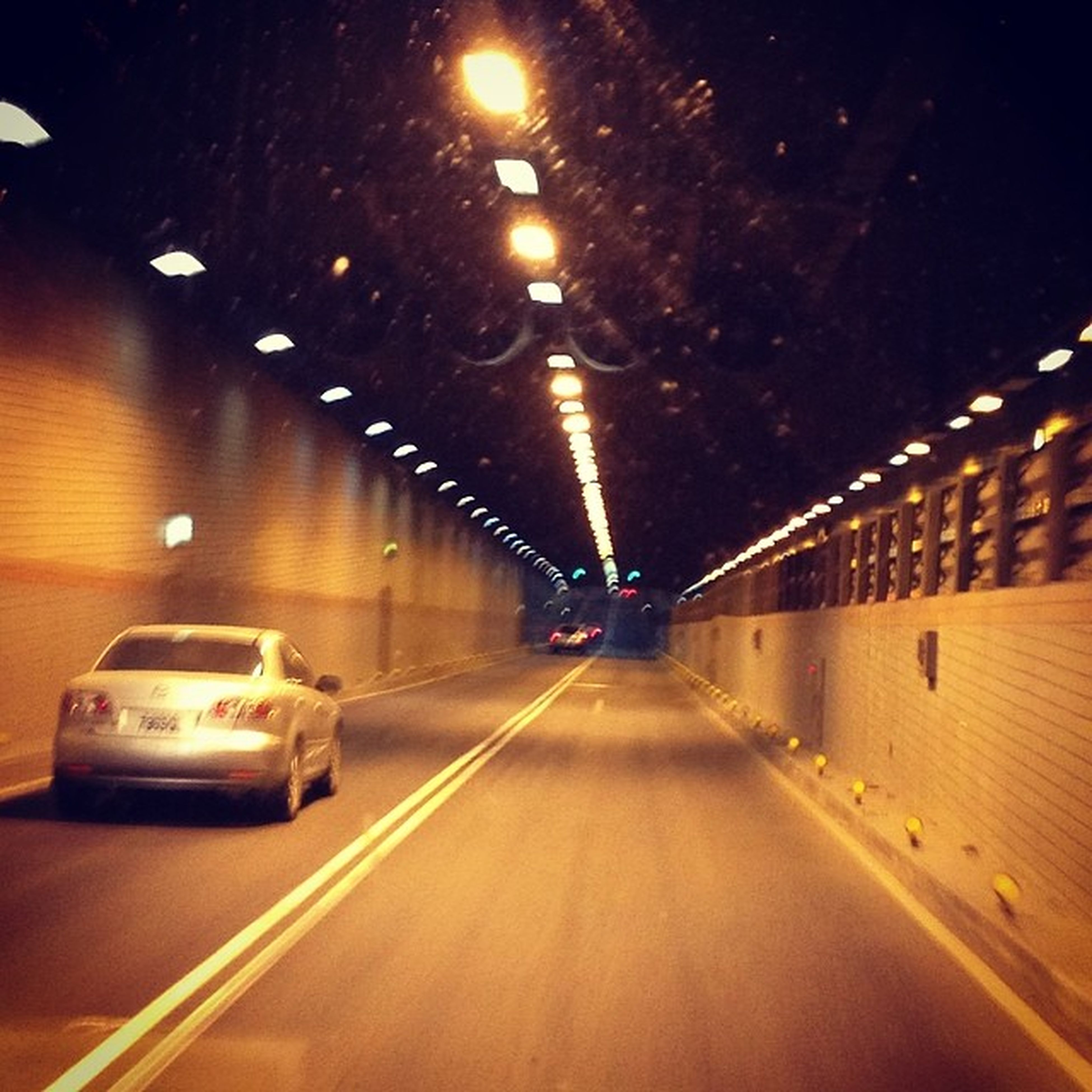 illuminated, night, the way forward, transportation, lighting equipment, diminishing perspective, road, vanishing point, street light, indoors, in a row, tunnel, road marking, motion, light - natural phenomenon, street, empty, glowing, electric light, no people