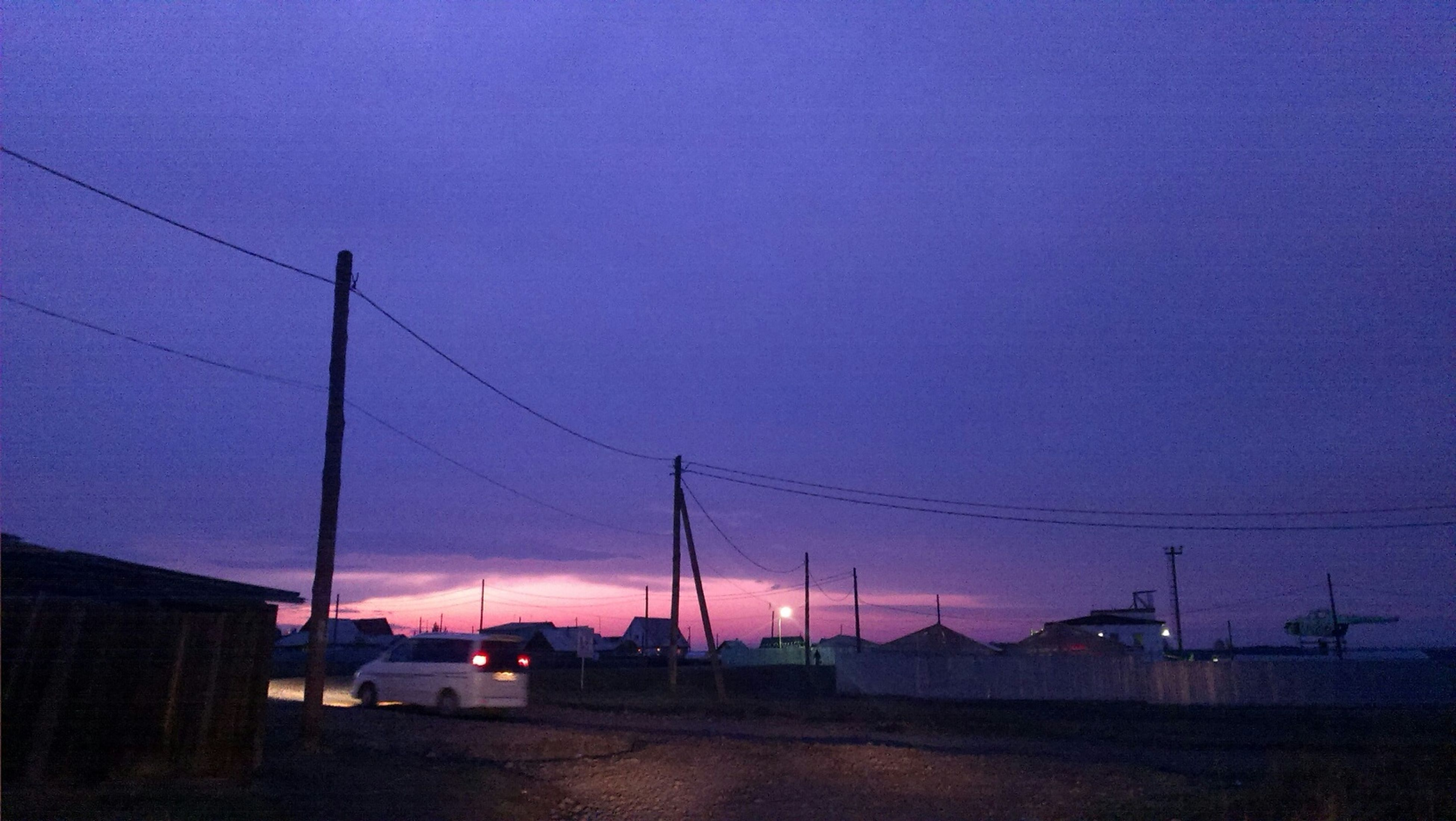 sunset, power line, electricity pylon, electricity, sky, building exterior, street light, power supply, built structure, cable, dusk, road, blue, silhouette, copy space, architecture, fuel and power generation, street, clear sky, transportation