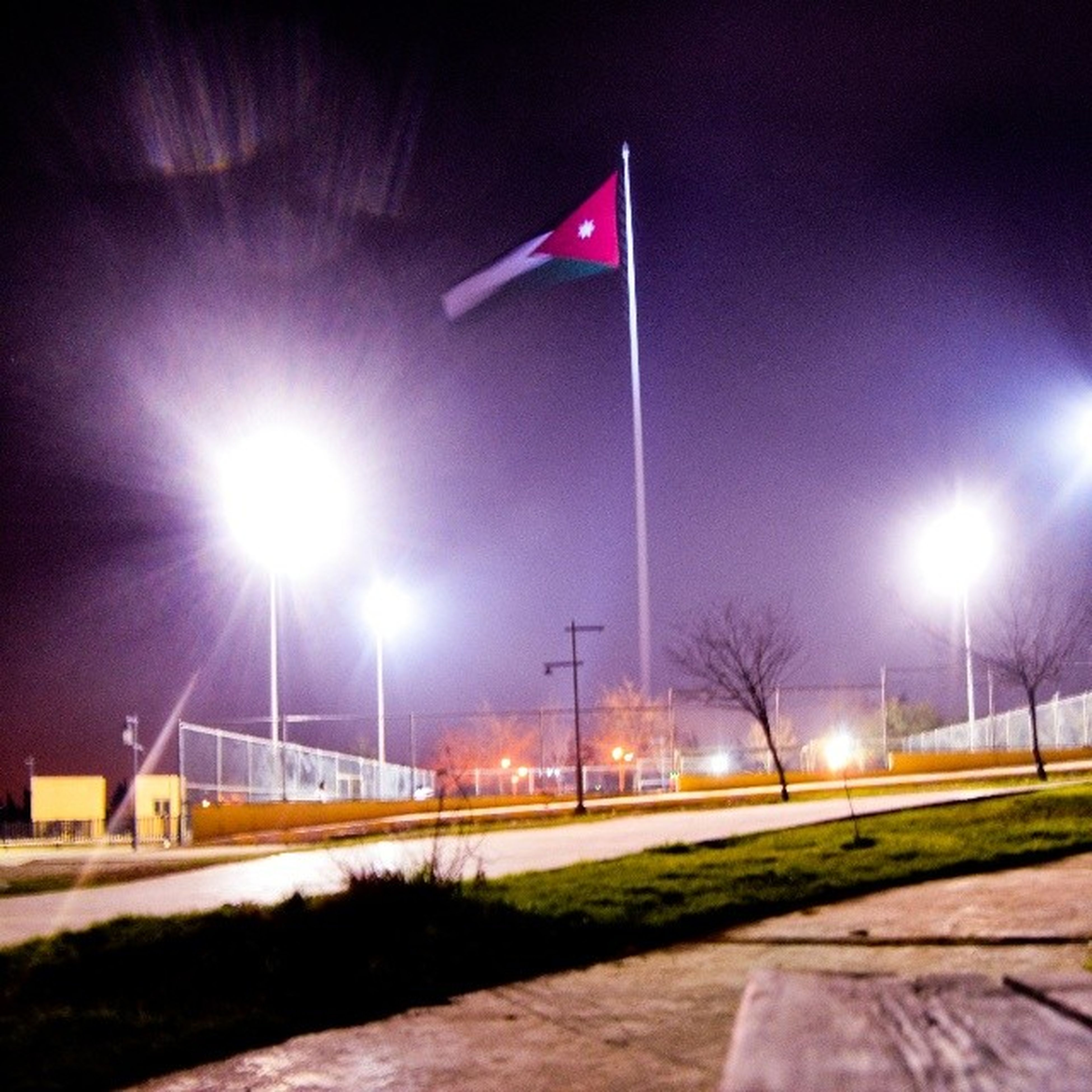 illuminated, night, street light, grass, road, sky, transportation, lighting equipment, field, no people, multi colored, outdoors, green color, flag, street, empty, the way forward, road marking, blue, long exposure
