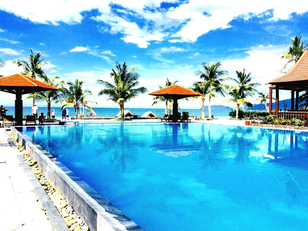 swimming pool, water, vacations, luxury hotel, tourist resort, relaxation, hotel, palm tree, luxury, tranquility, day, architecture, outdoors, built structure, sea, sky, beauty in nature, nature, no people, swimming, tree