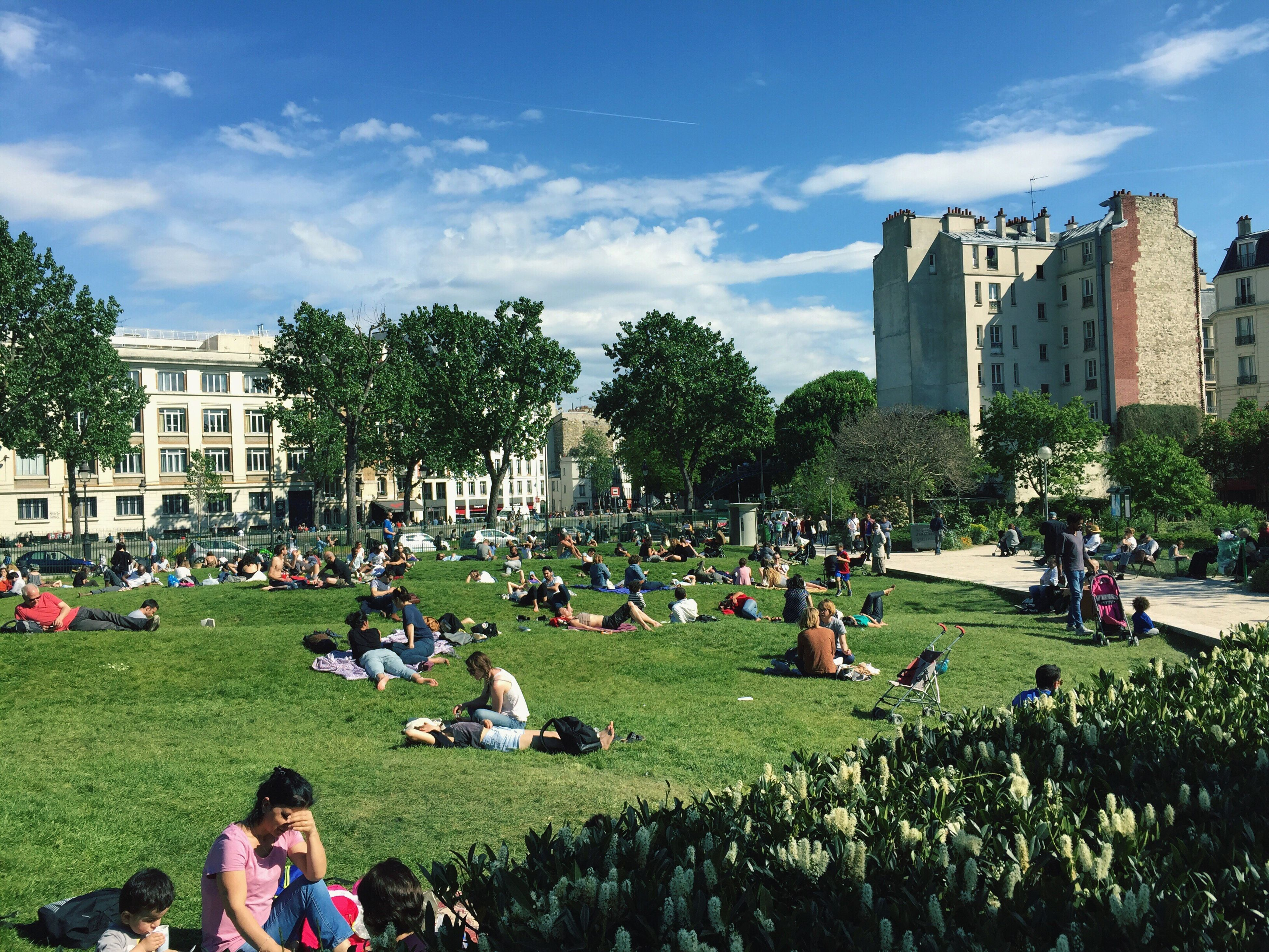 large group of people, lifestyles, leisure activity, person, men, tree, grass, building exterior, architecture, sky, mixed age range, relaxation, built structure, crowd, park - man made space, enjoyment, sitting, city, city life