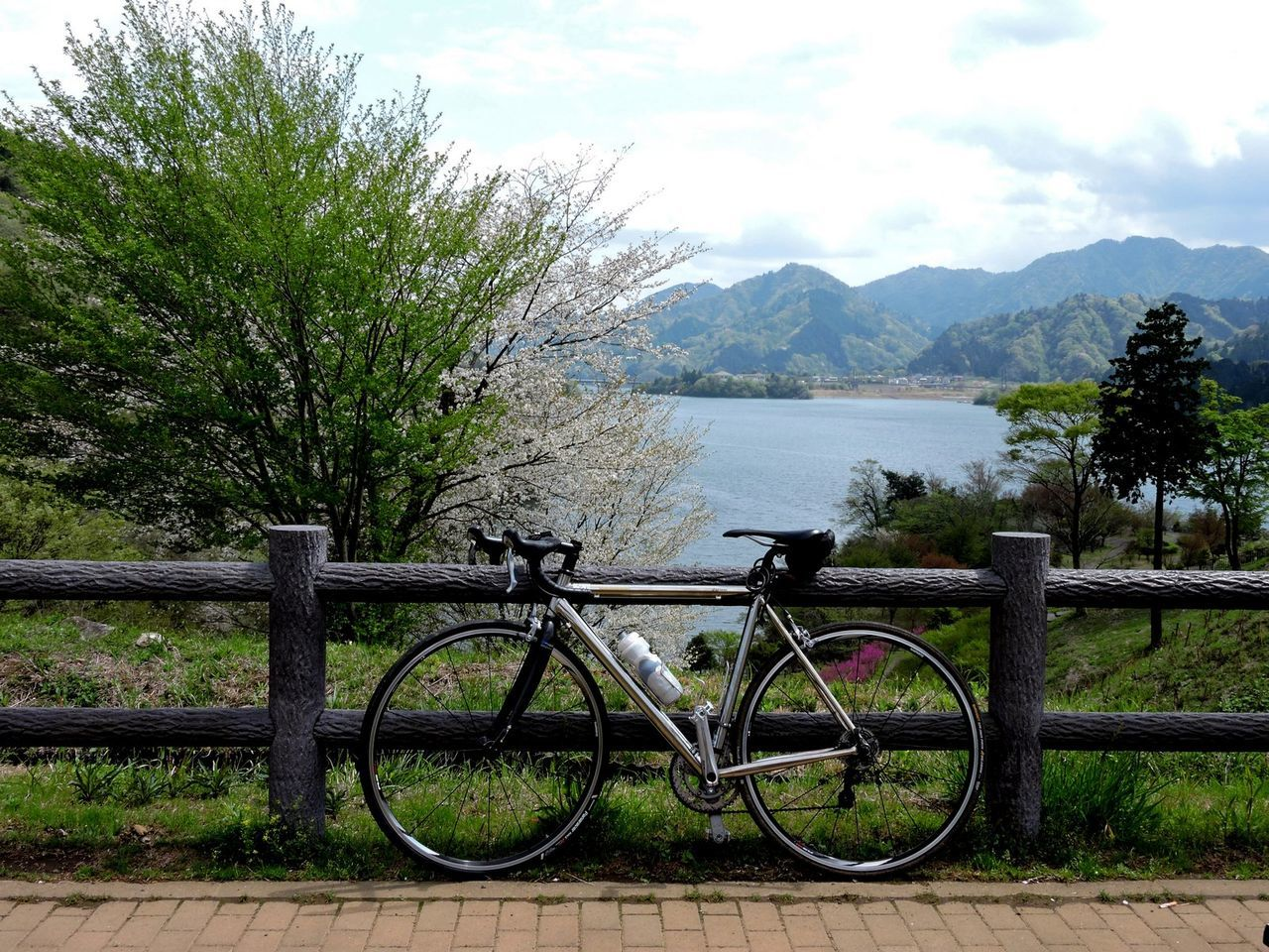 Beauty In Nature Bicycle Blue Hills Grass Idyllic Lake View Landscape No People Non-urban Scene Outdoors Railing Fence Tranquil Scene Waterbottle